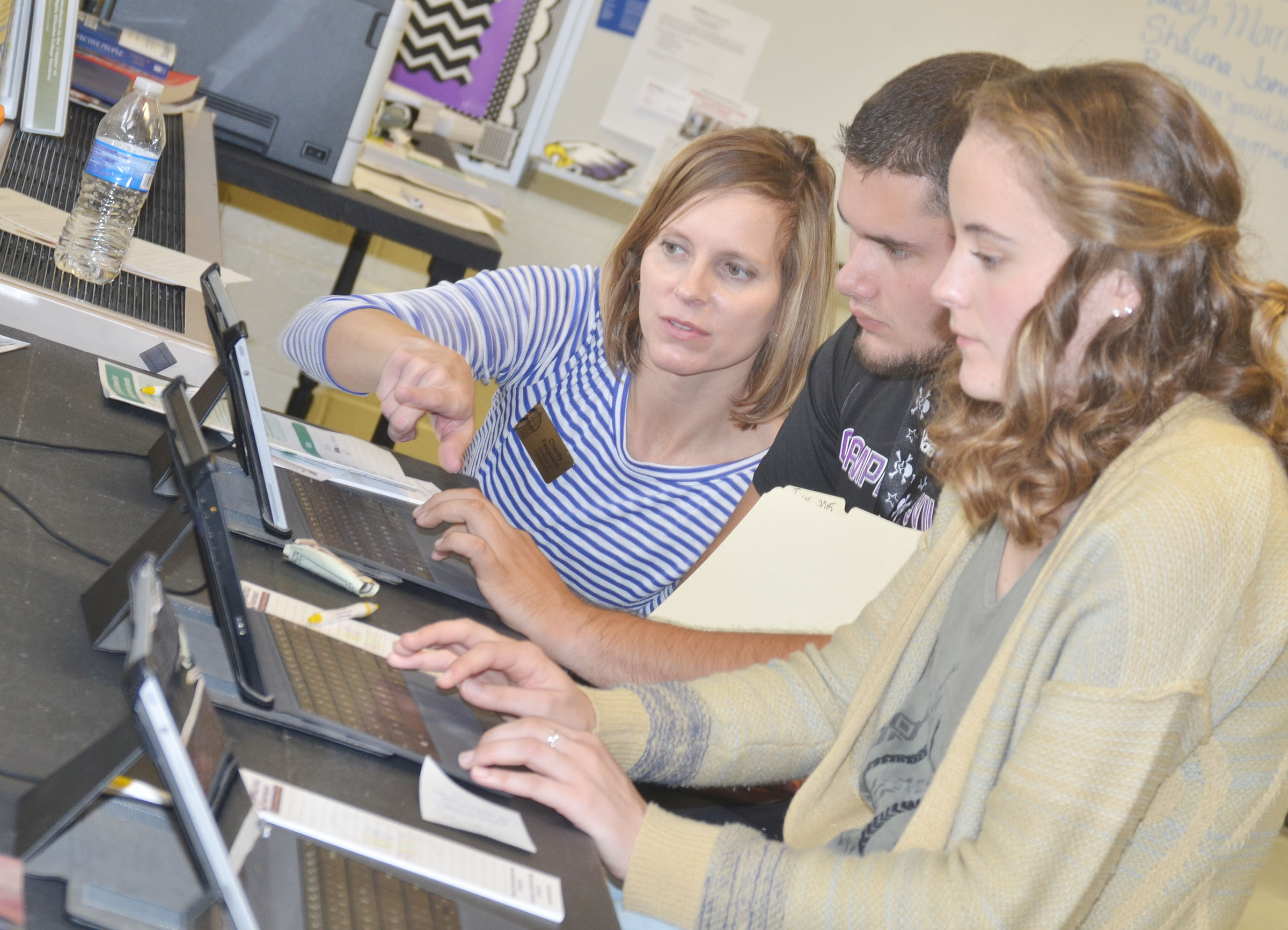Charity Ferguson, director of admissions at Lindsey Wilson College, helps seniors Logan Brown, center, and Caroline McMahan with their FAFSAs.