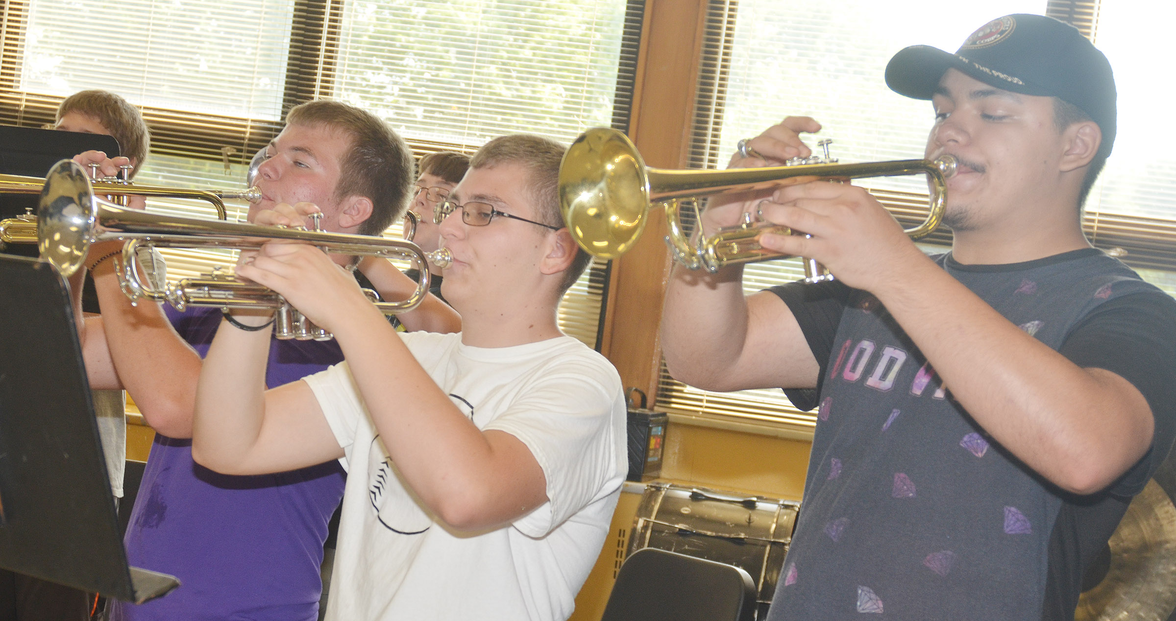 From left, trumpet players Josh Dooley, Brandon Greer and Nick Cowan, juniors, practice during a rehearsal.