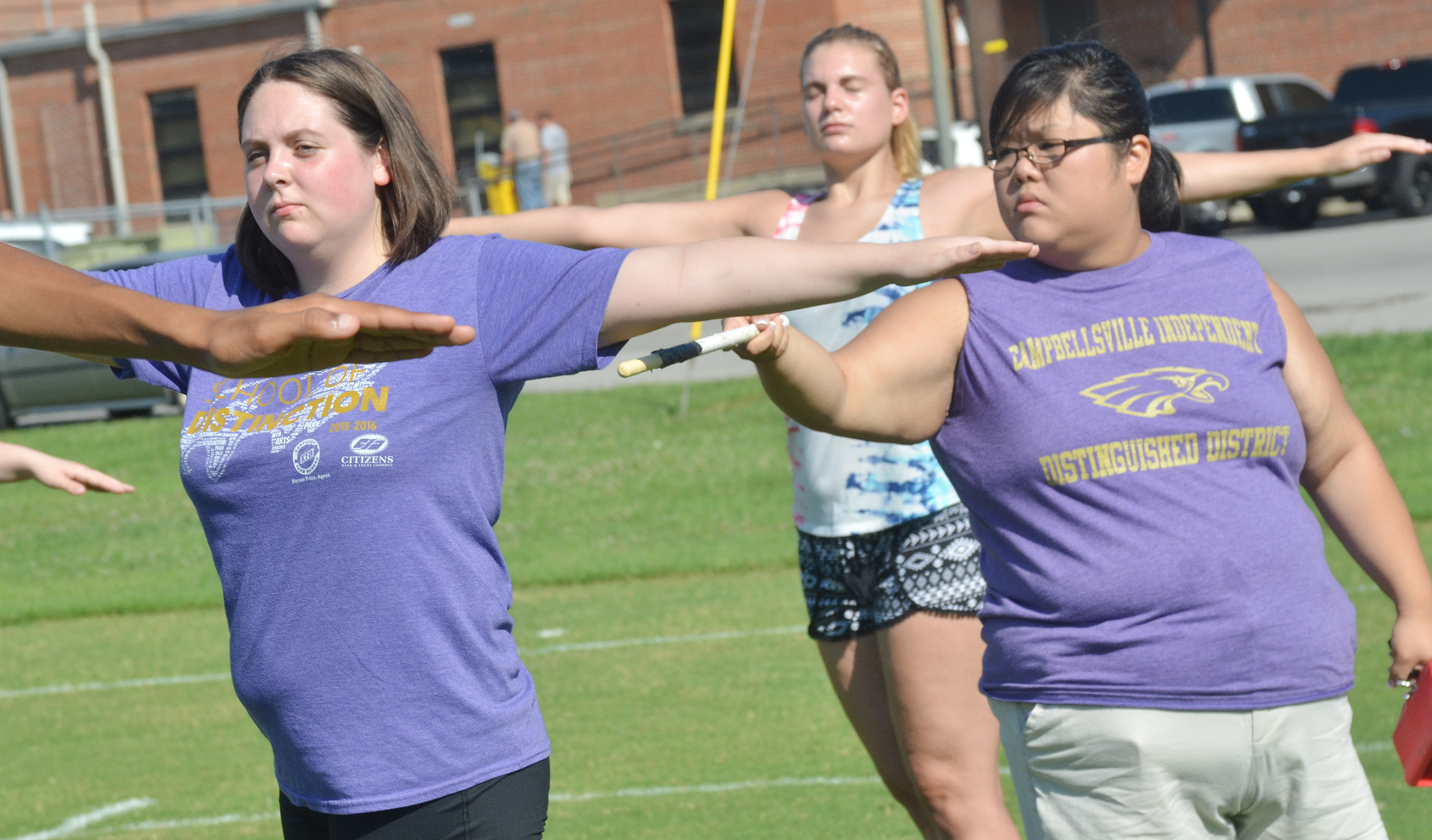 Assistant Band Director Brittany Johnson straightens junior Ruby Hatfield's arms during fundamentals.