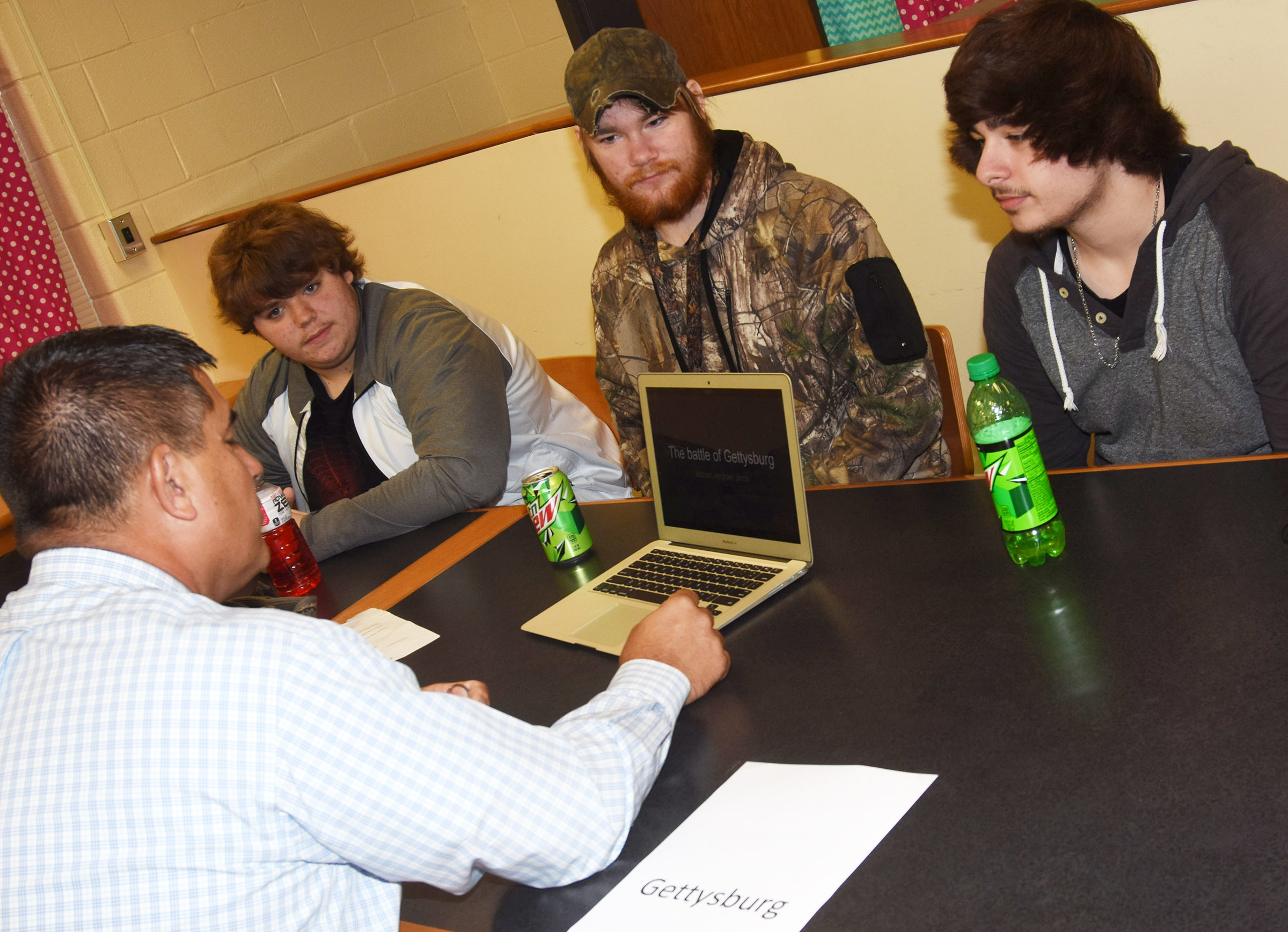Campbellsville Independent Schools Superintendent Kirby Smith talks with, from left, CHS juniors Nathan Anderson, Michael Milburn and Jacob Mattingly about their project on the Gettysburg war.