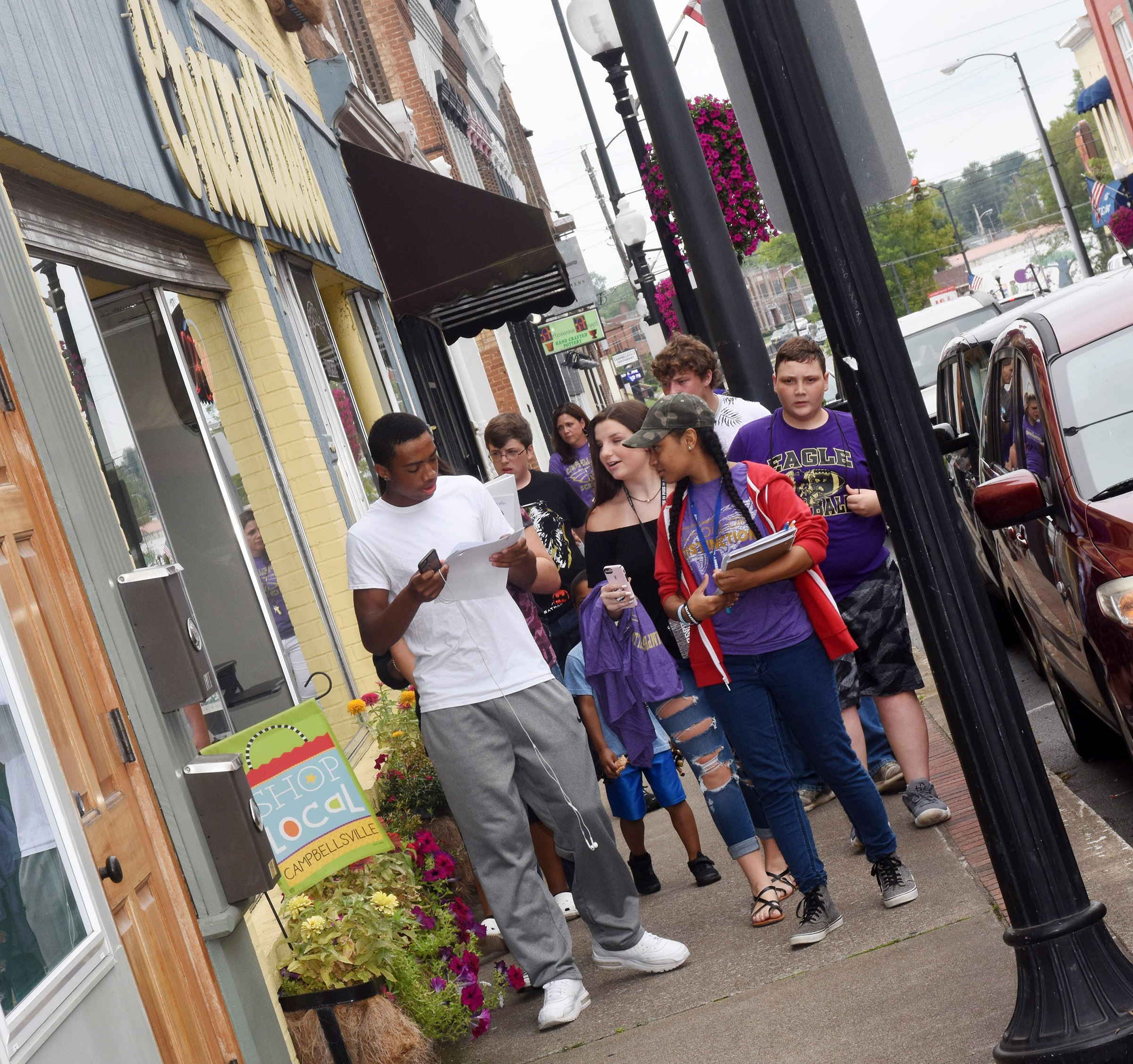 CHS students walk downtown as they deliver thank you notes and t-shirts to local businesses.