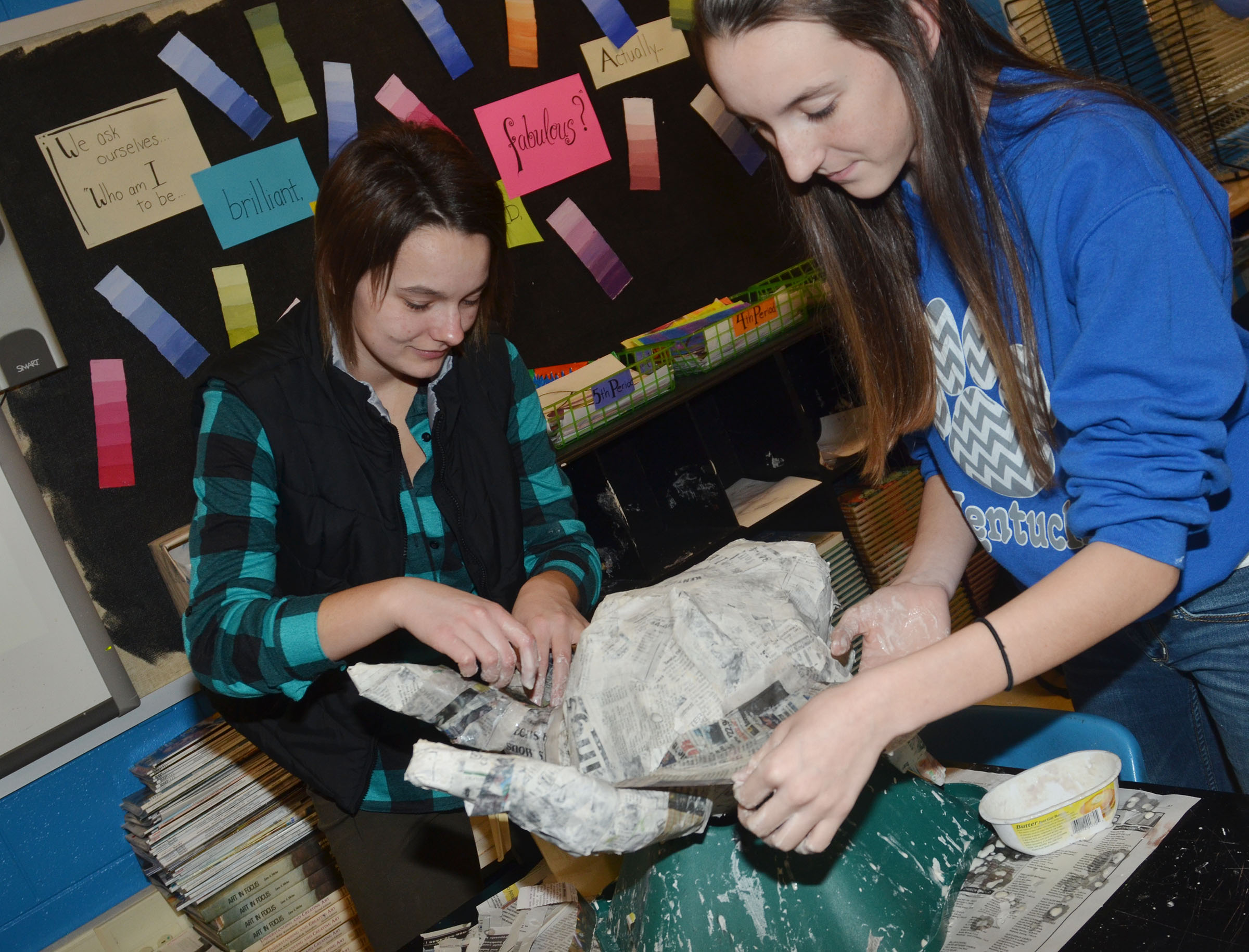 CHS senior Kyrsten Hill, at left, and sophomore Zoe McAninch form their paper mache sculpture.