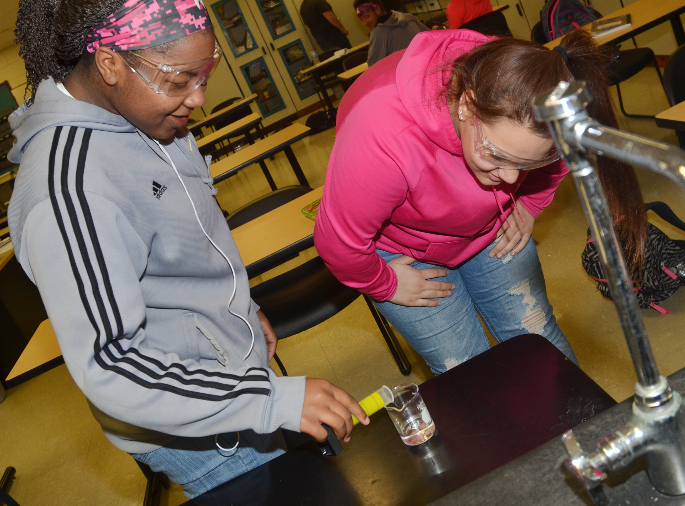 CHS junior Nena Barnett, at left, pours hydrochloric acid on her group's pennies as classmate Jayden Bridgewater watches.