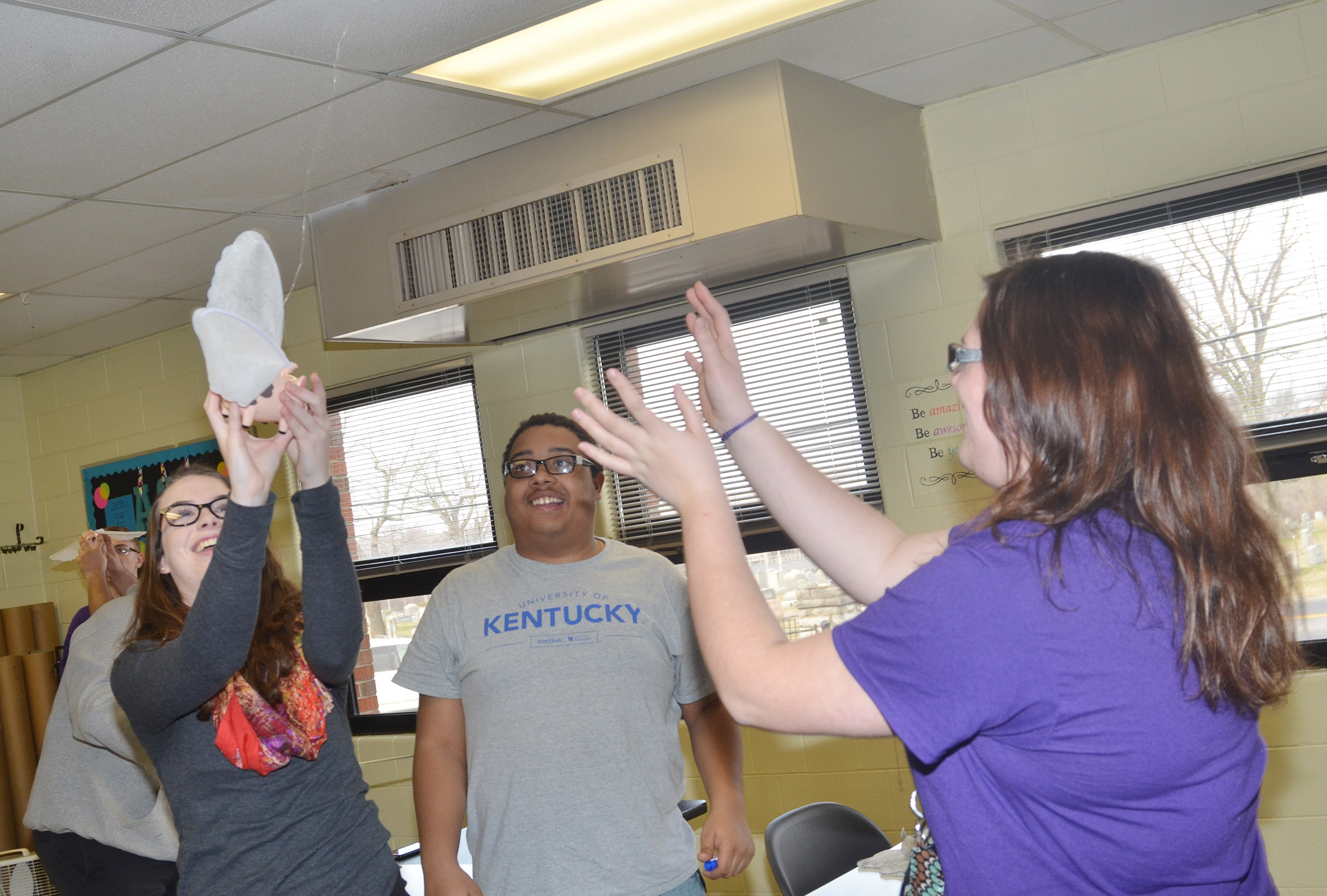 "CHS seniors, from left, Laura Lamb, Ricky Smith-Cecil and Vera Brown laugh as their pig ""flies."""