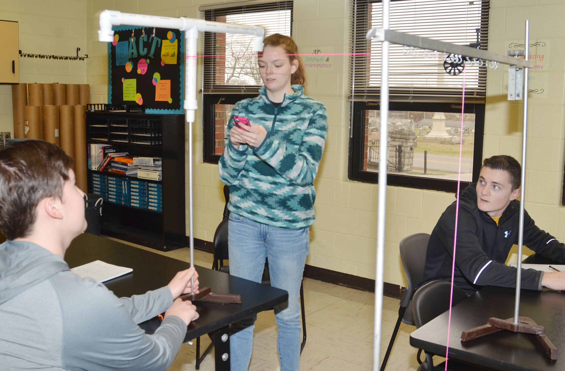 CHS seniors Zack Settle, at left, and Blair Lamb perform their experiment as junior Bryce Richardson looks on.