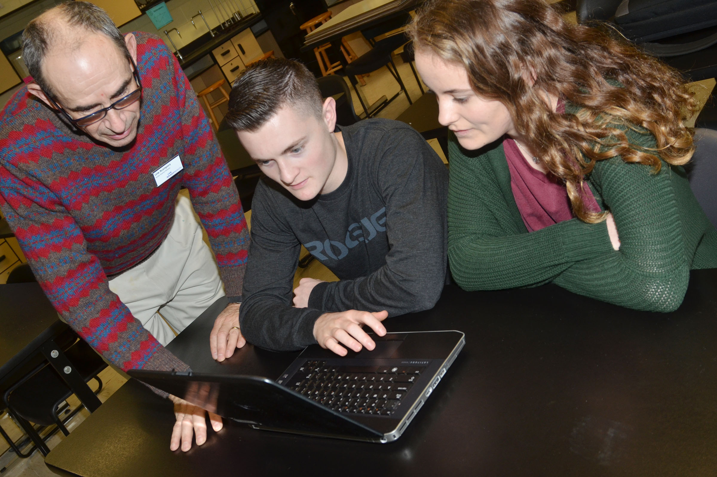 Lew Acampora, senior science director with AdvanceKentucky, helps CHS junior Bryce Richardson and senior Caroline McMahan as they analyze data with the Logger Pro software.