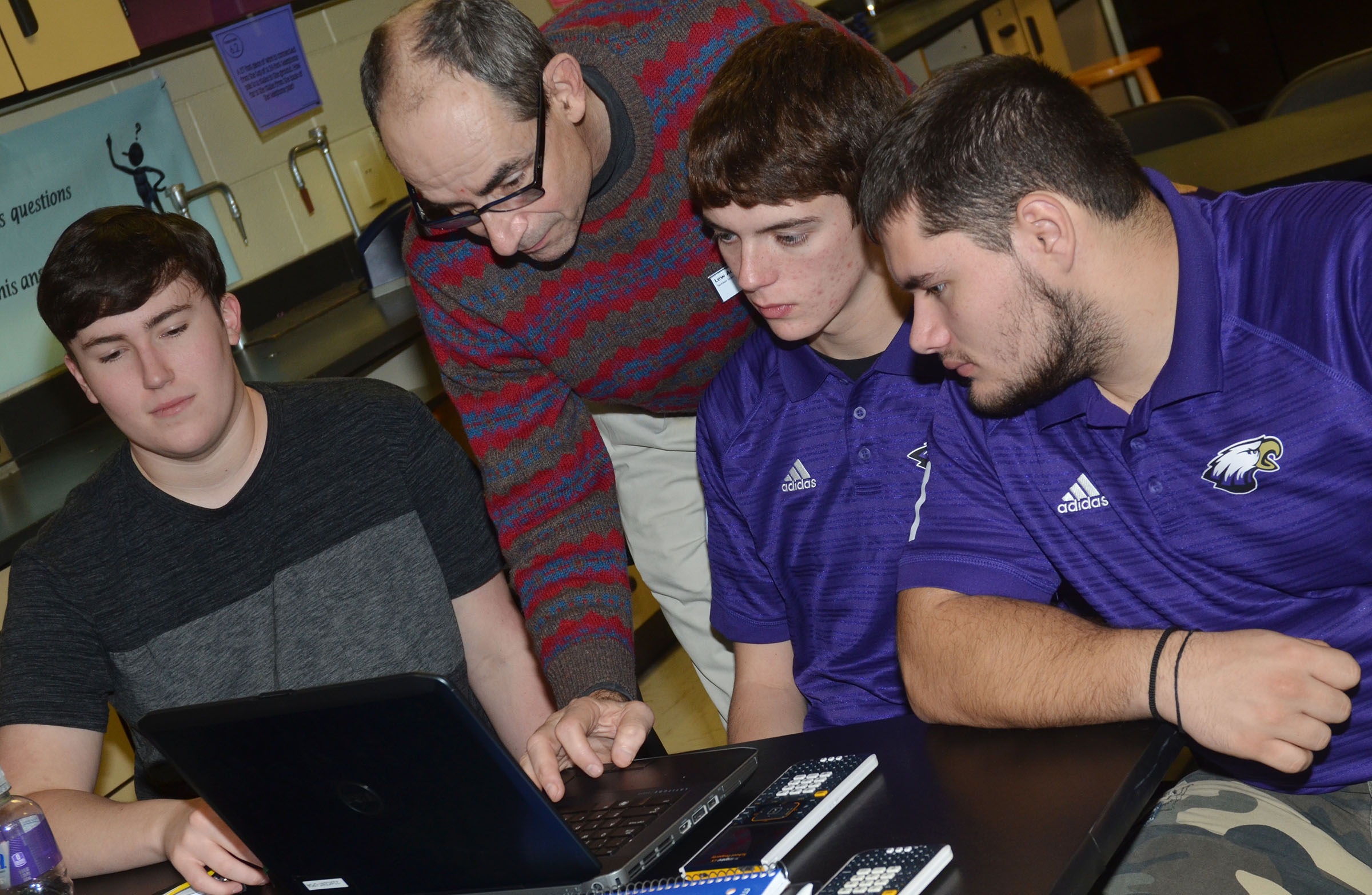 Lew Acampora, senior science director with AdvanceKentucky, works with CHS seniors, from left, Zack Settle, Murphy Lamb and Logan Brown as they learn the Logger Pro software.