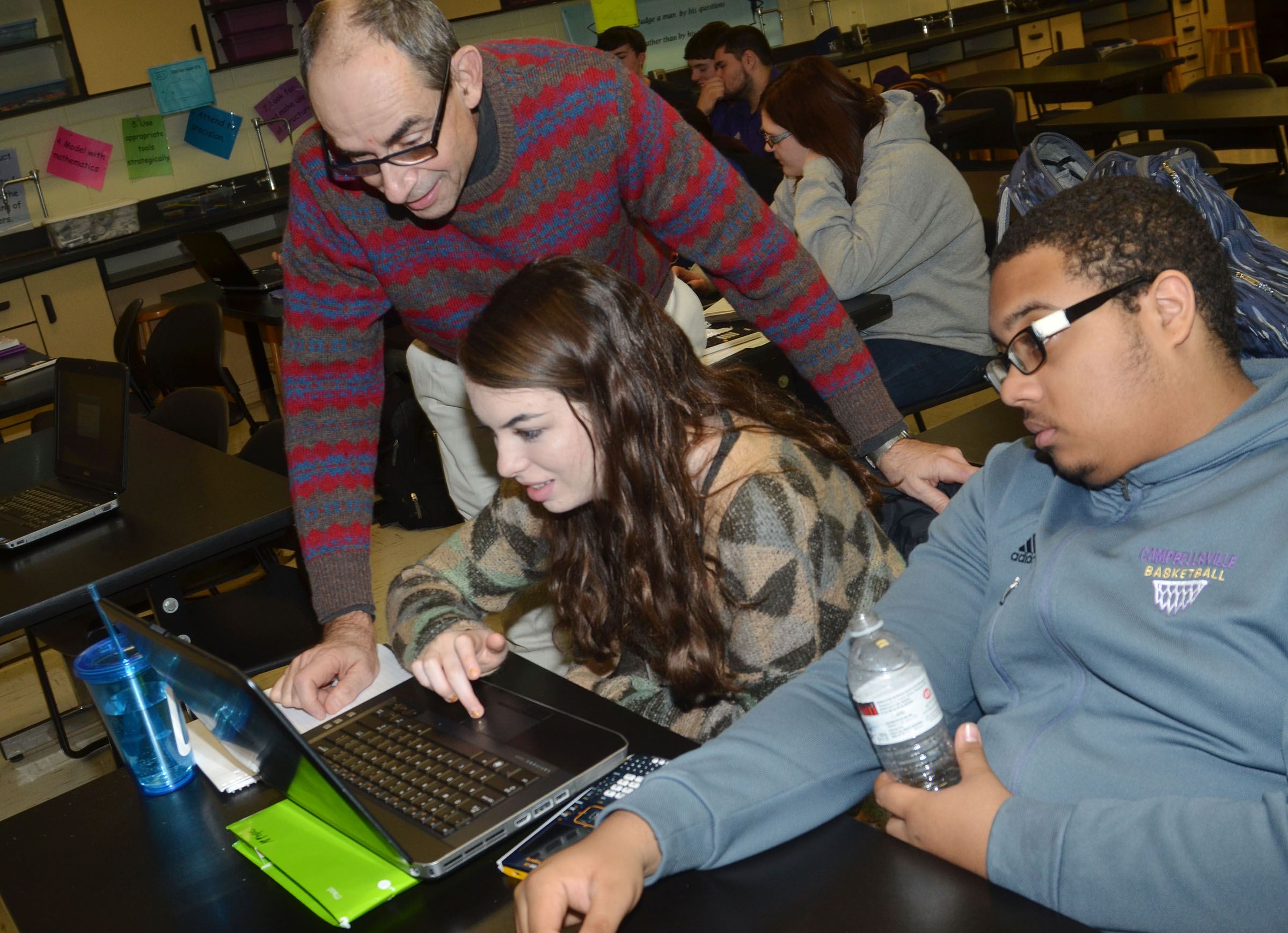 Lew Acampora, senior science director with AdvanceKentucky, helps CHS seniors Laura Lamb and Ricky Smith-Cecil use the Logger Pro software.
