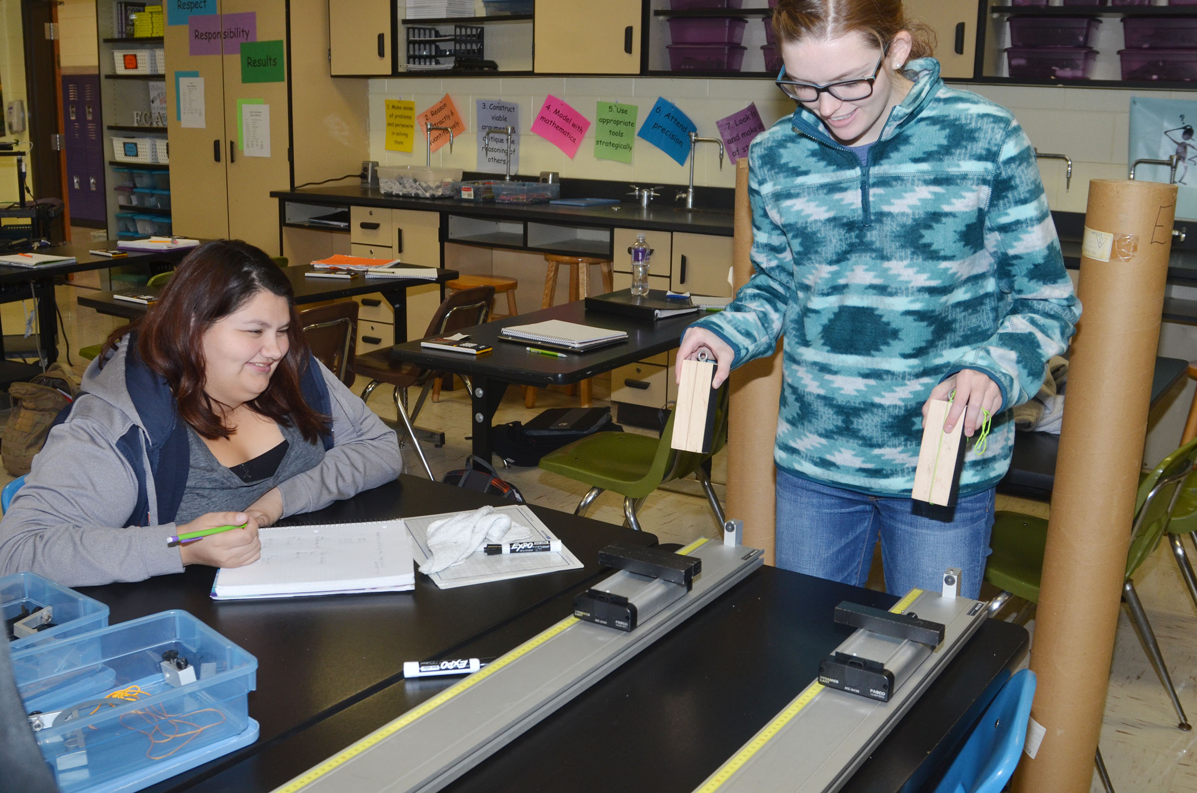 CHS senior Laura May Gutierrez, at left, records data as classmate Blair Lamb tests how much mass and momentum are required to make their carts travel at the same speed.