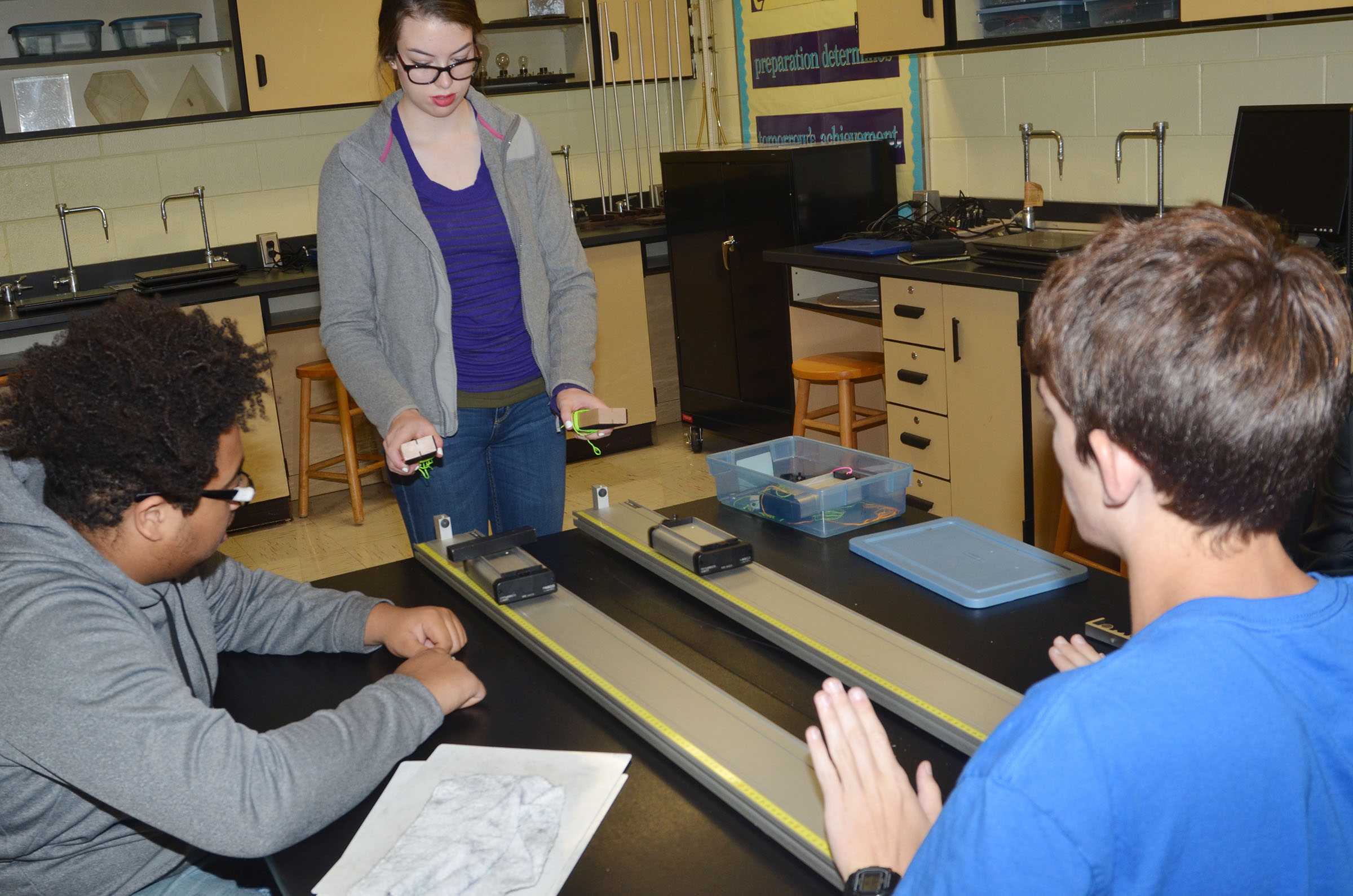 CHS senior Laura Lamb and her groupmates, seniors Ricky Smith-Cecil, at left, and Murphy Lamb perform their momentum lab experiment.