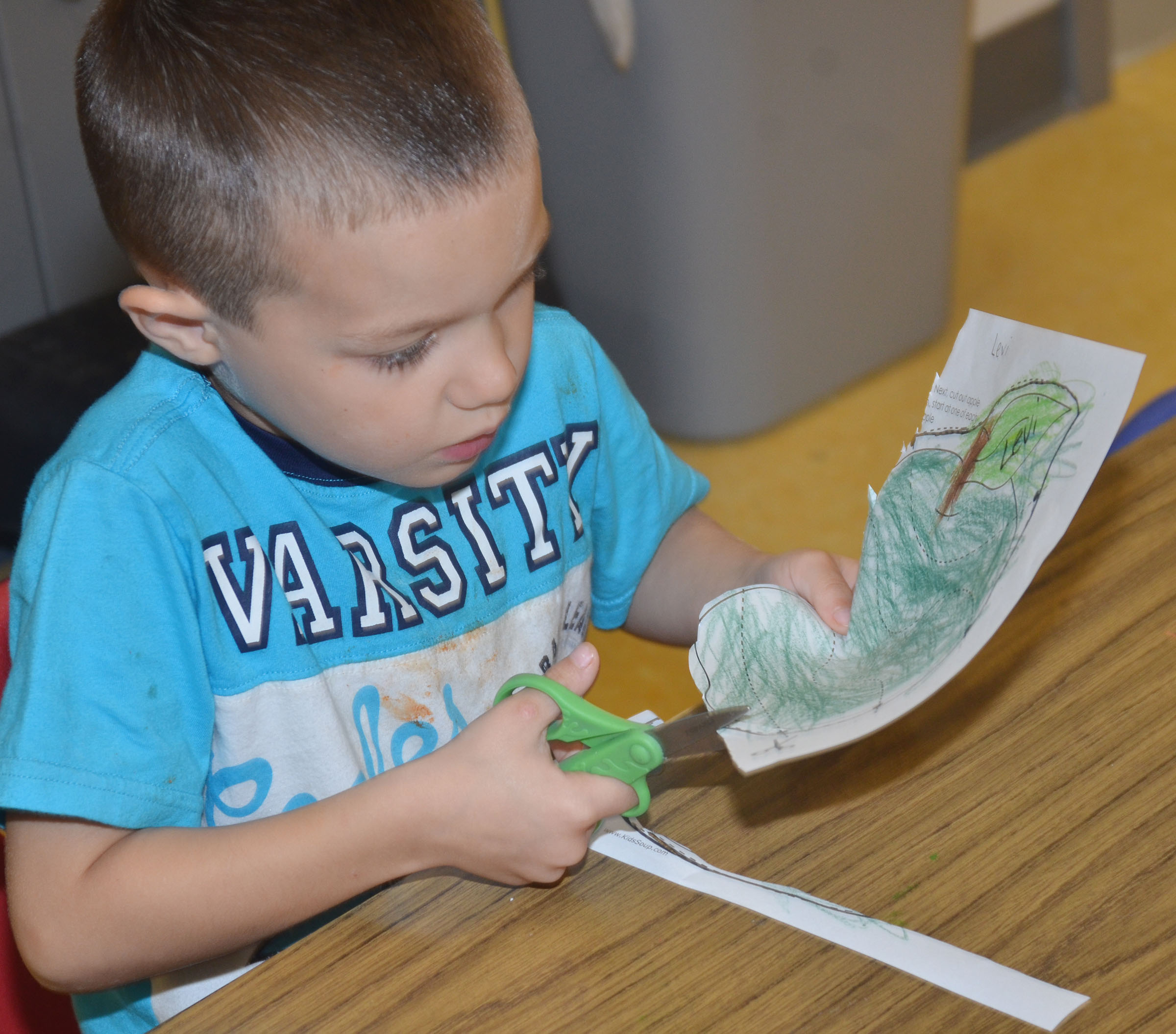 CES preschool student Levi Ritchie cuts out his apple puzzle.