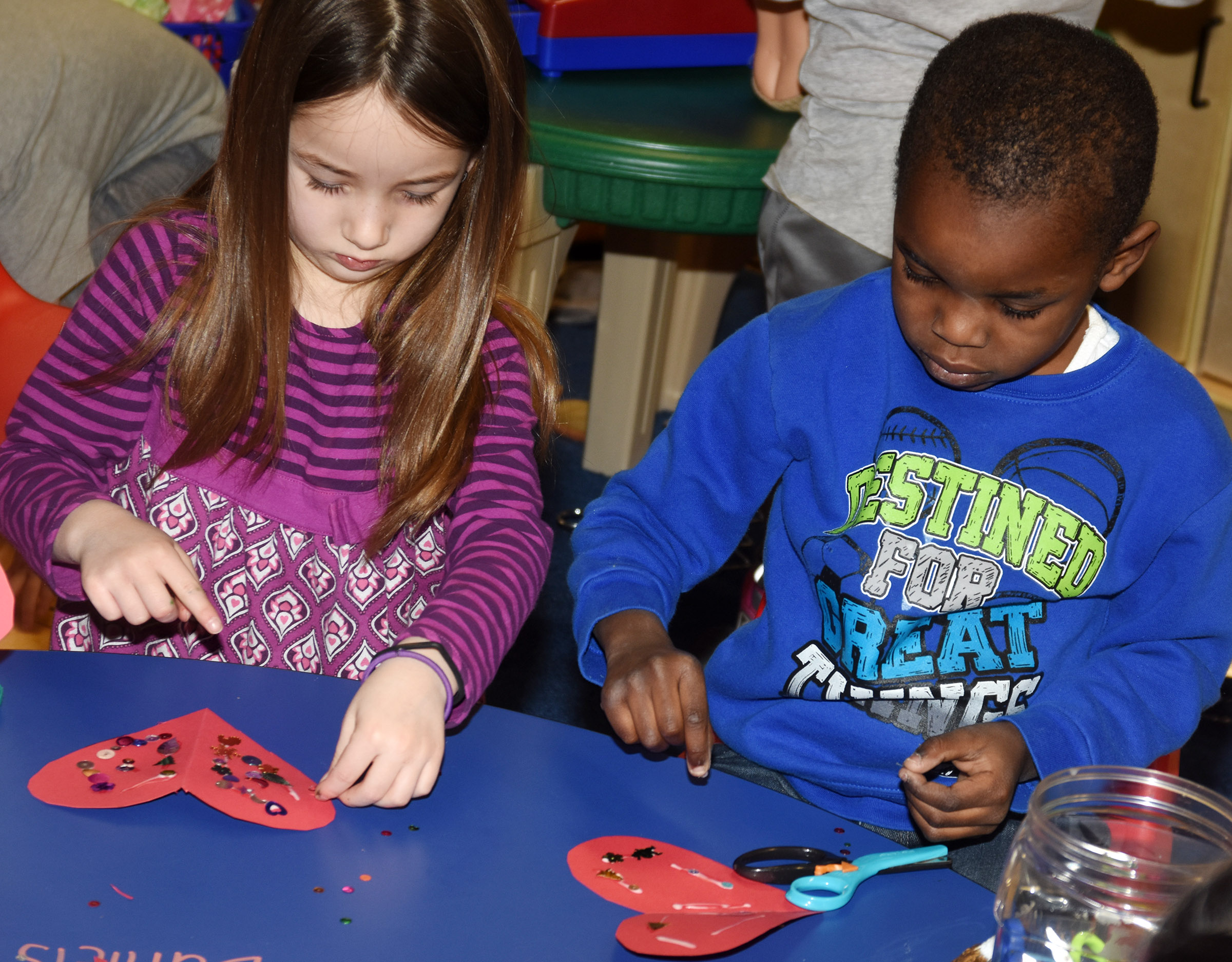 CES preschool students Lylah Davis, at left, and Xavien Smith decorate Valentine cards.