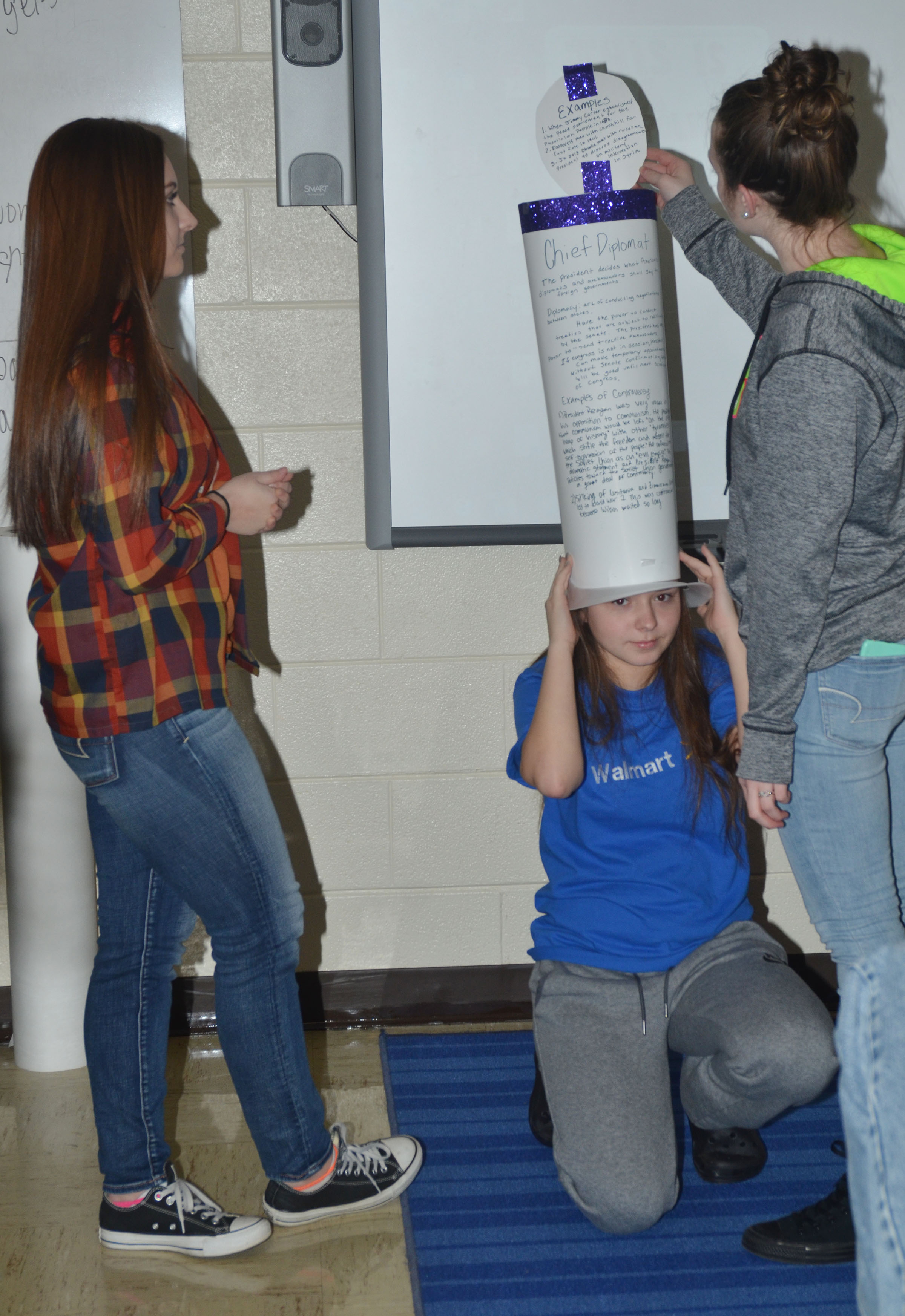 CHS sophomore Christa Riggs wears her group's presidential hat as Reagan Knight, at left, and Caleigh Bright discuss it.