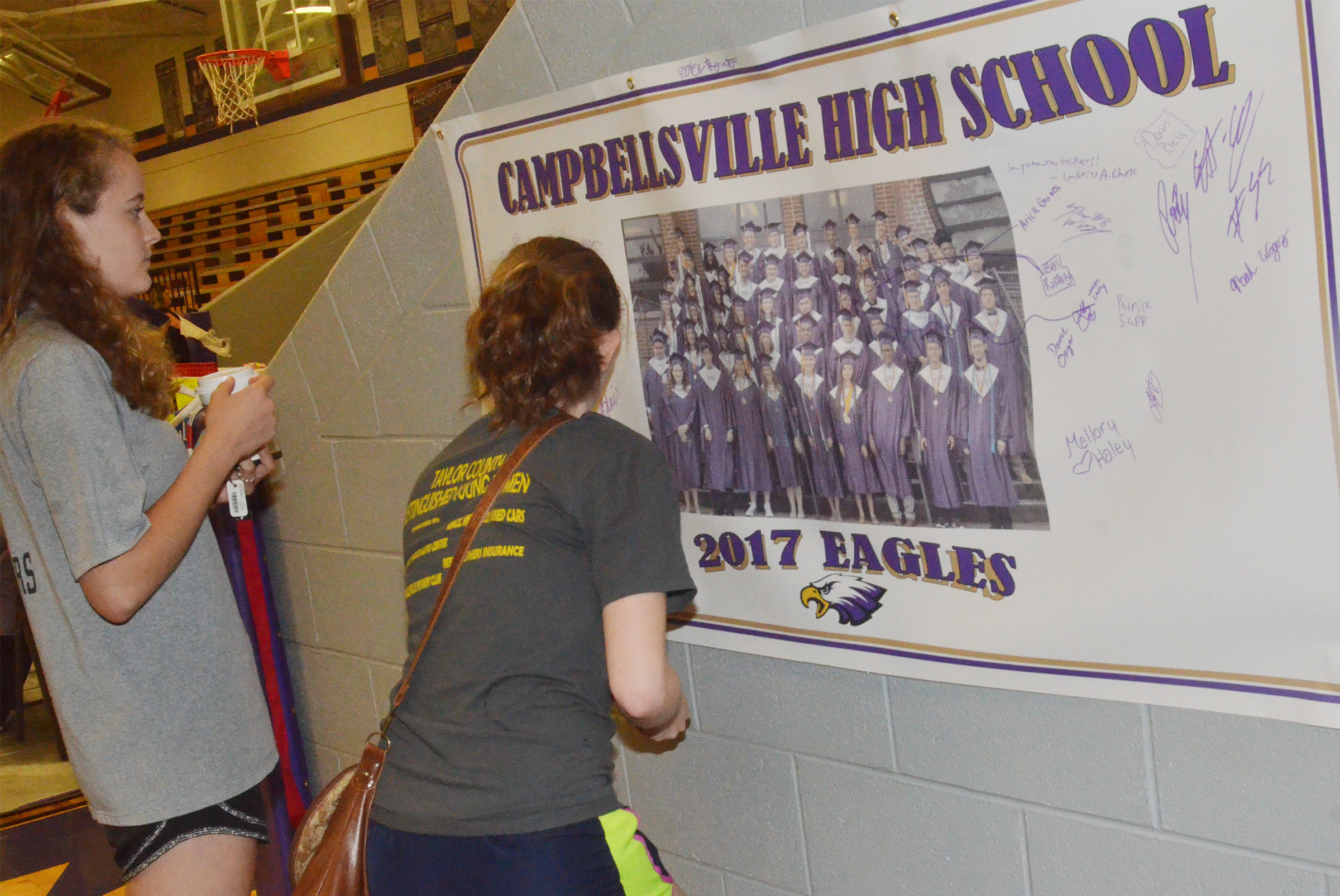 CHS seniors Caroline McMahan, at left, and Blair Lamb sign a banner featuring a photo of their graduating class.