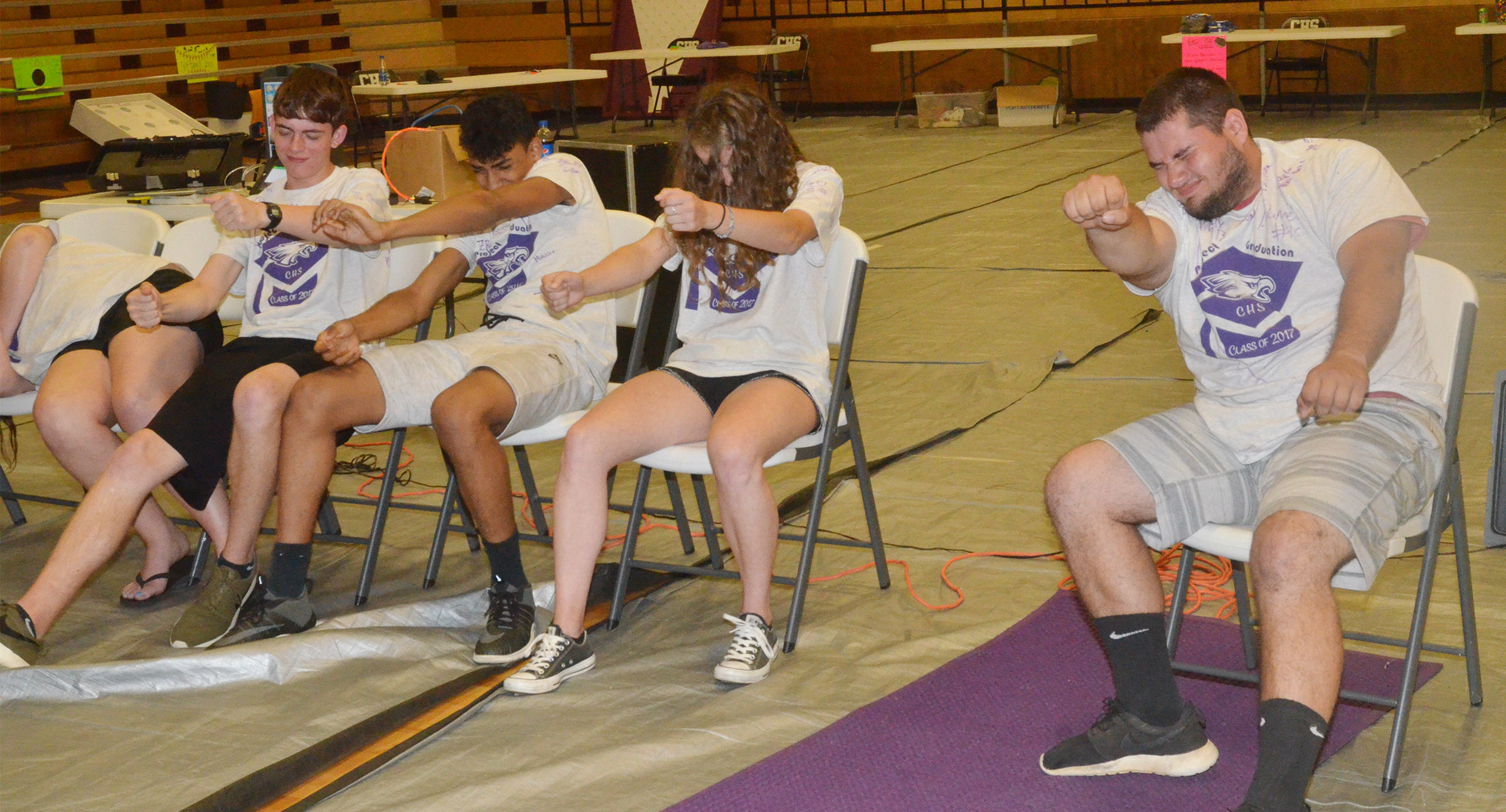 CHS seniors, from left, Murphy Lamb, Daniel Silva, Caroline McMahan and Logan Brown drive racecars while under hypnosis.