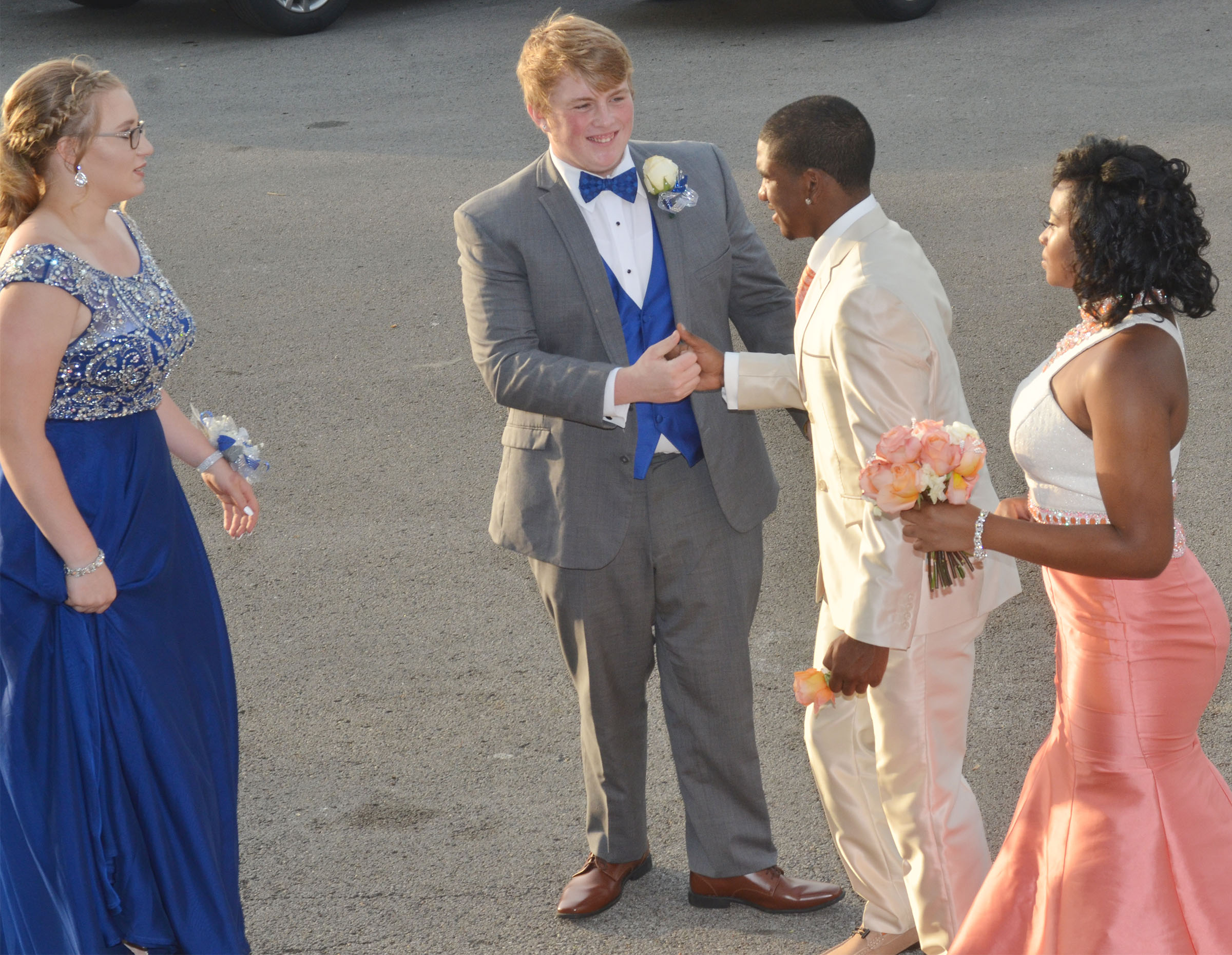 CHS junior Ryan Jeffries greets classmate Tyrion Taylor as they walk into CHS for prom walk. At left is Jeffries's date, freshman Samantha Johnson, and at right is Taylor's date Vonnea Smith, also a junior.