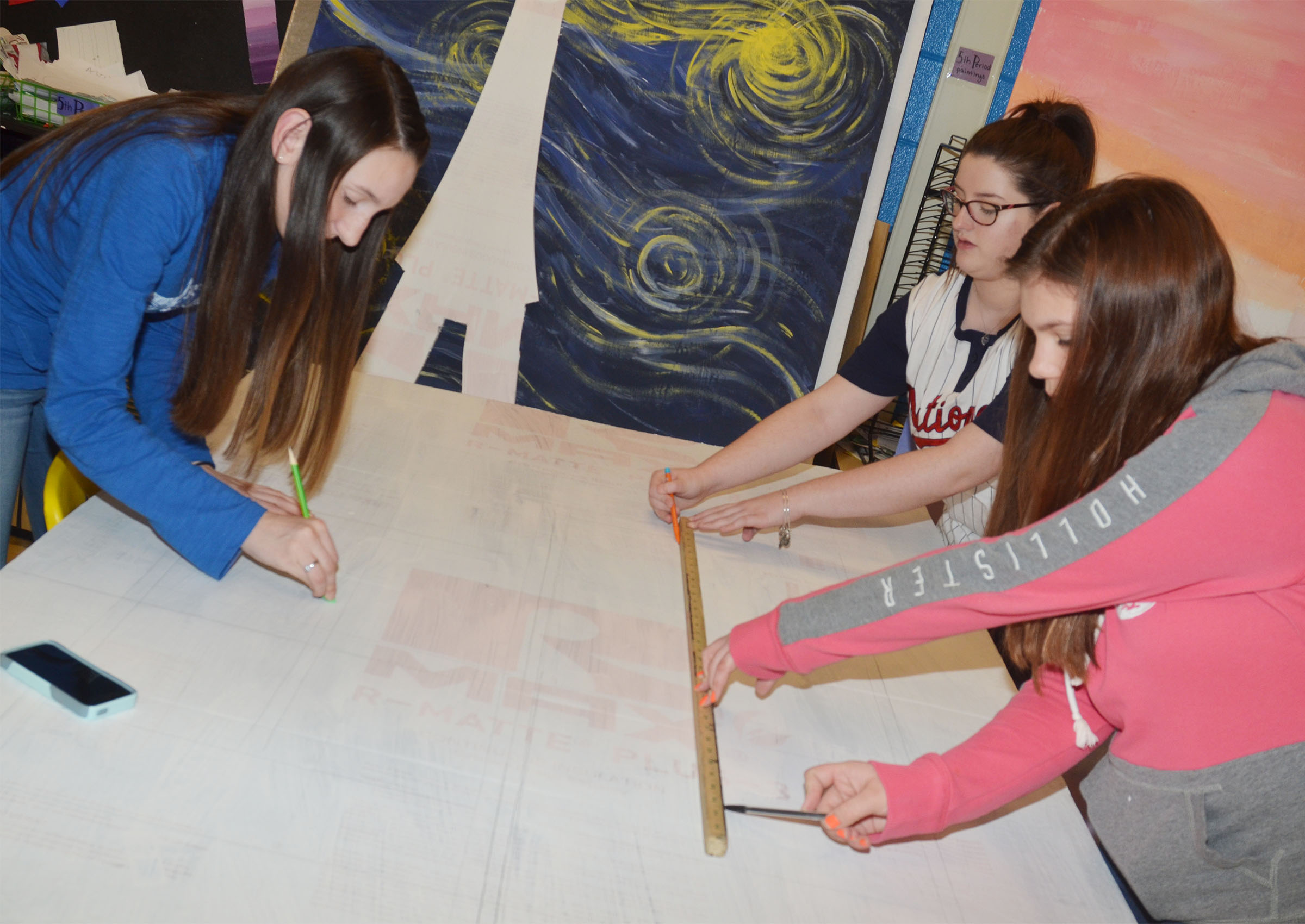 From left, CHS freshmen Zoe McAninch, Alli Wilson and Shelby Hunt work on a prom prop.