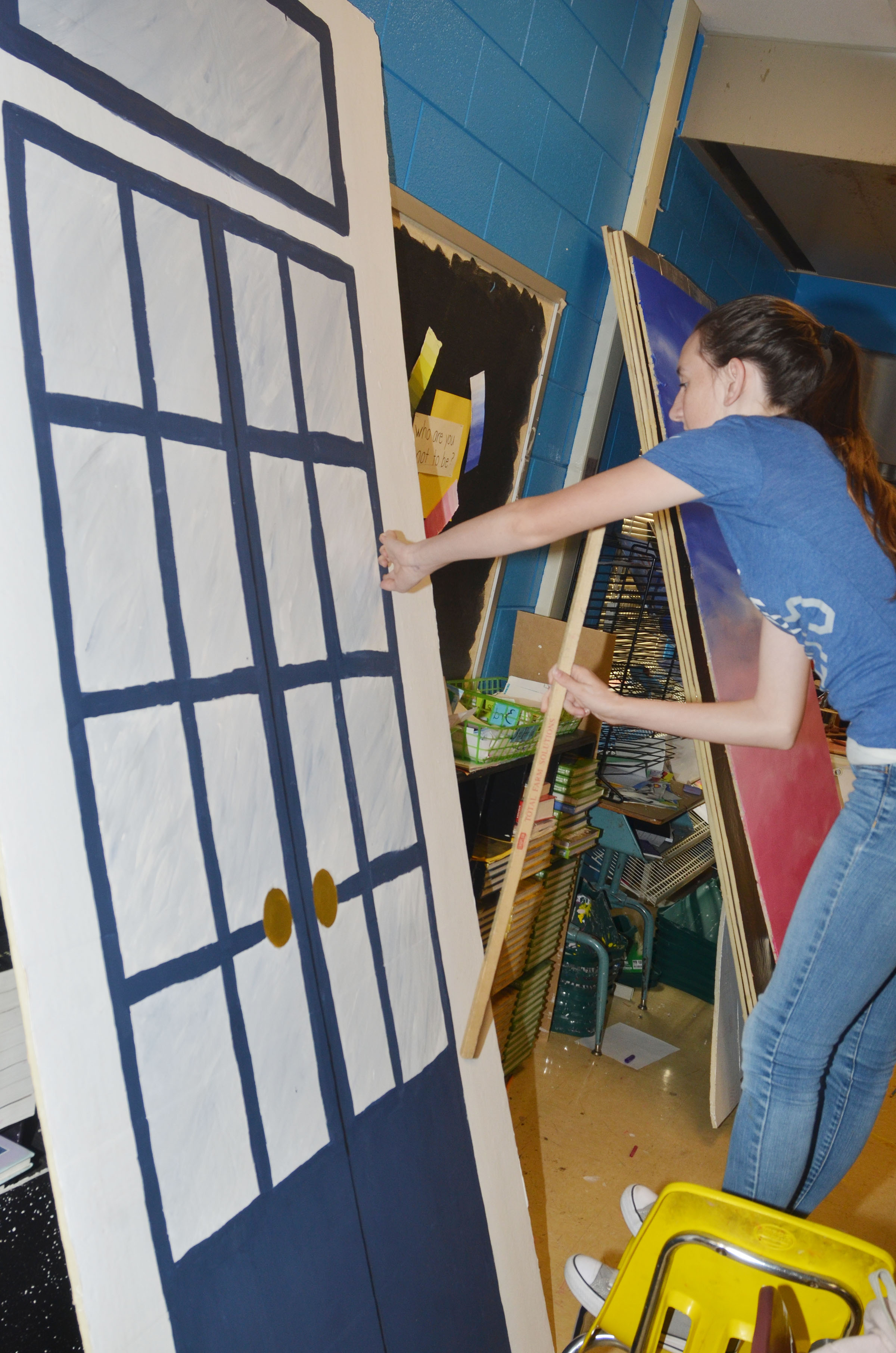CHS freshman Zoe McAninch measures a door on this prom prop.