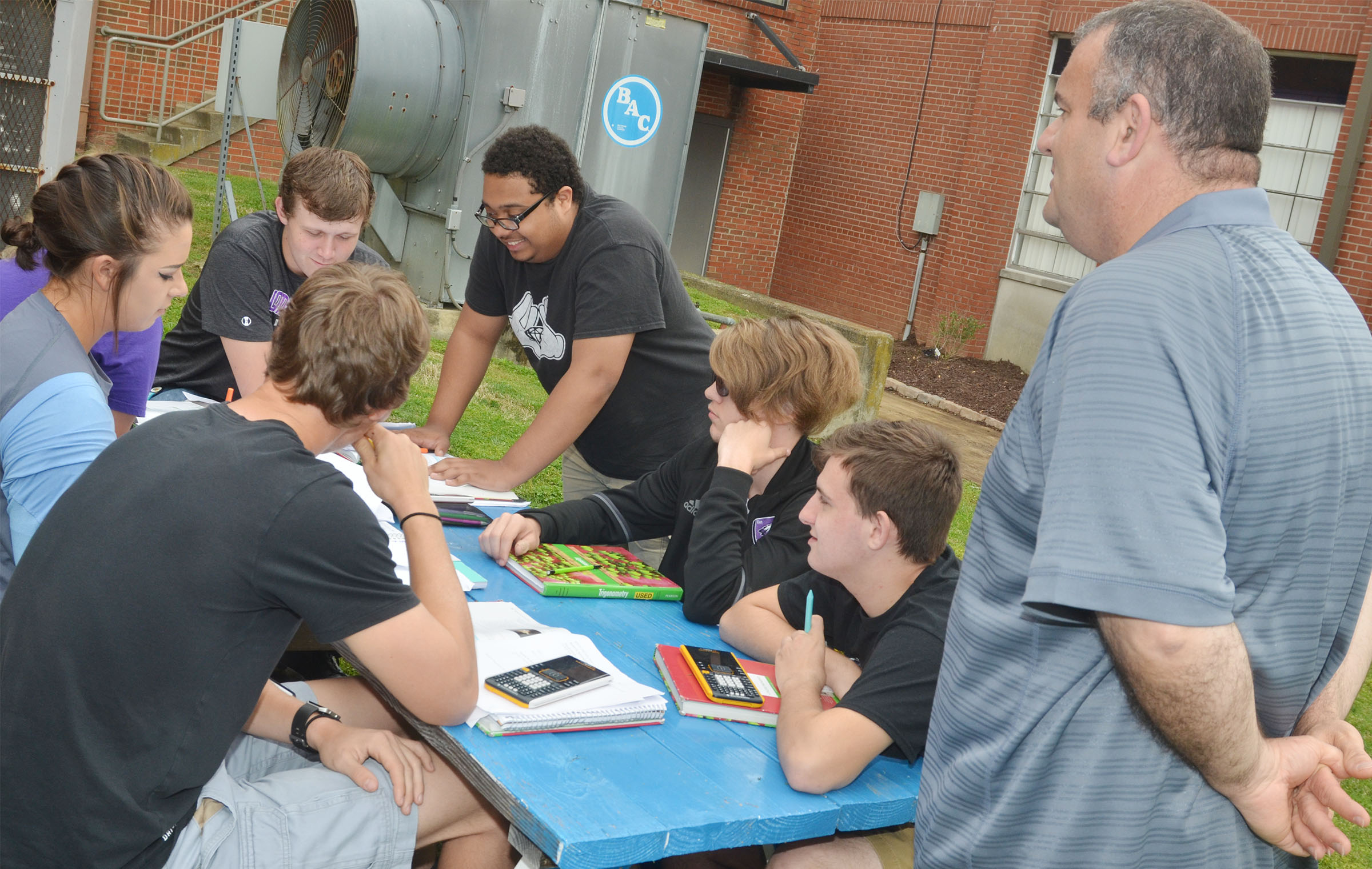CHS math teacher Kevin Rafferty talks to his students as they complete their homework while having class outside.