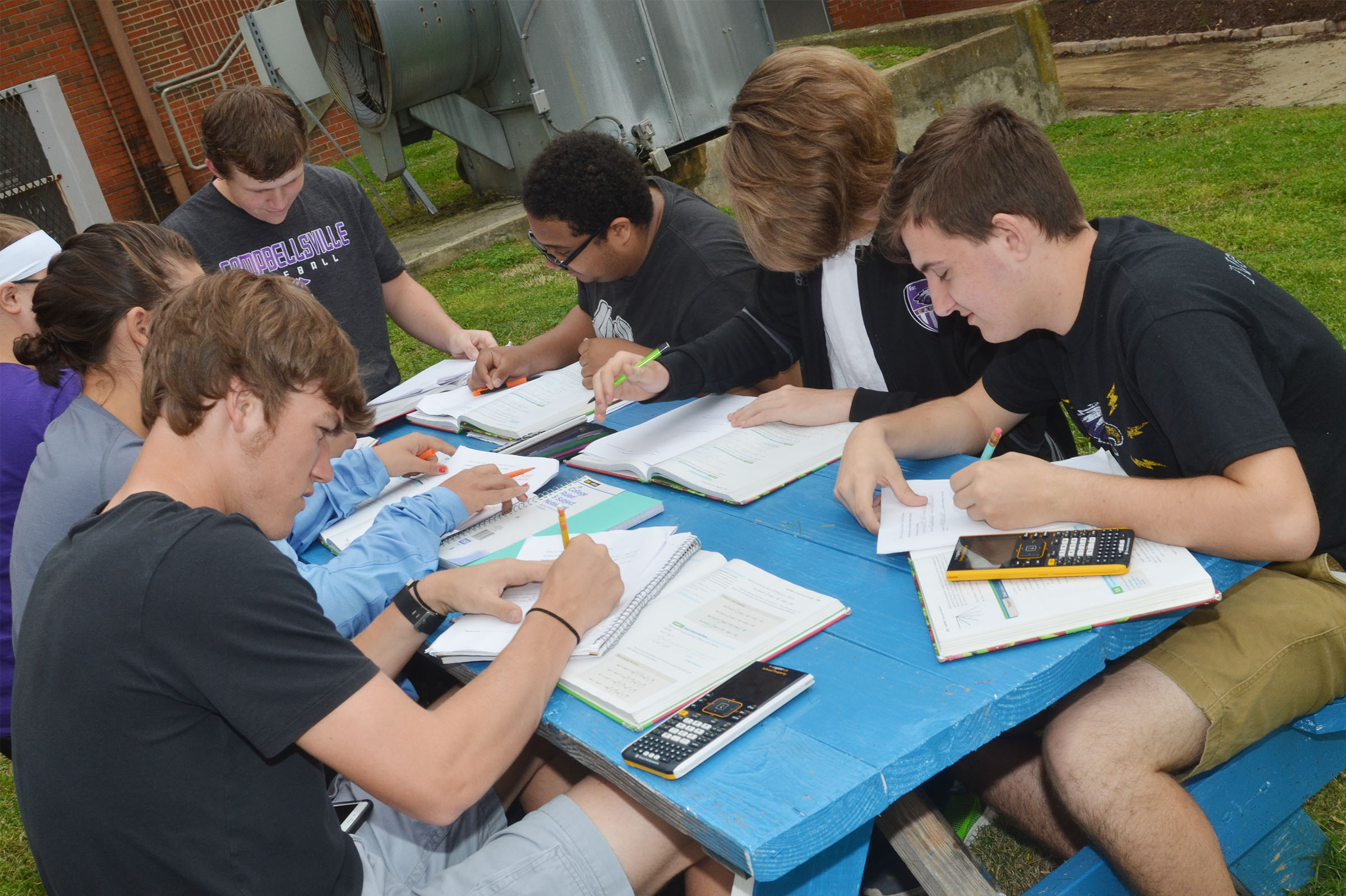CHS students complete homework while having trigonometry class outside. At left is senior Zack Bottoms and at right is junior Austin Fitzgerald.