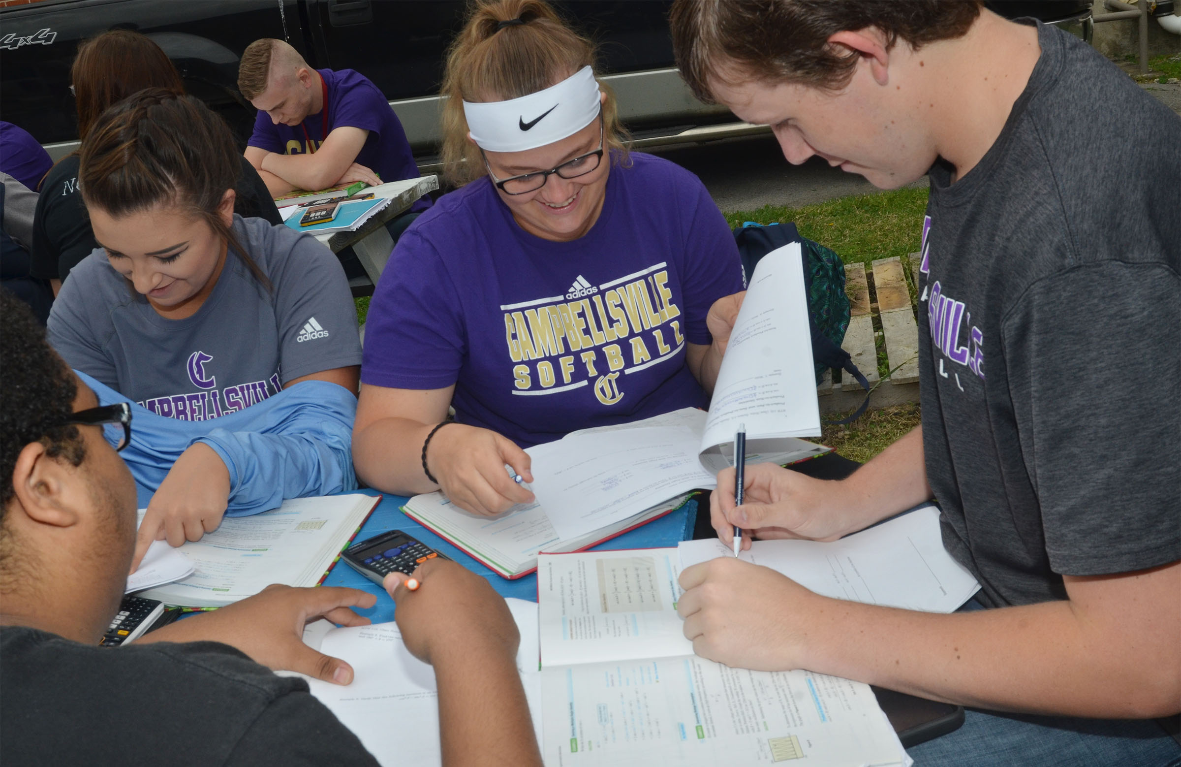 CHS seniors, from left, Kailey Morris, Brenna Wethington and Jared Brewster, and, in front, Ricky Smith-Cecil, work on their homework while having class outside.