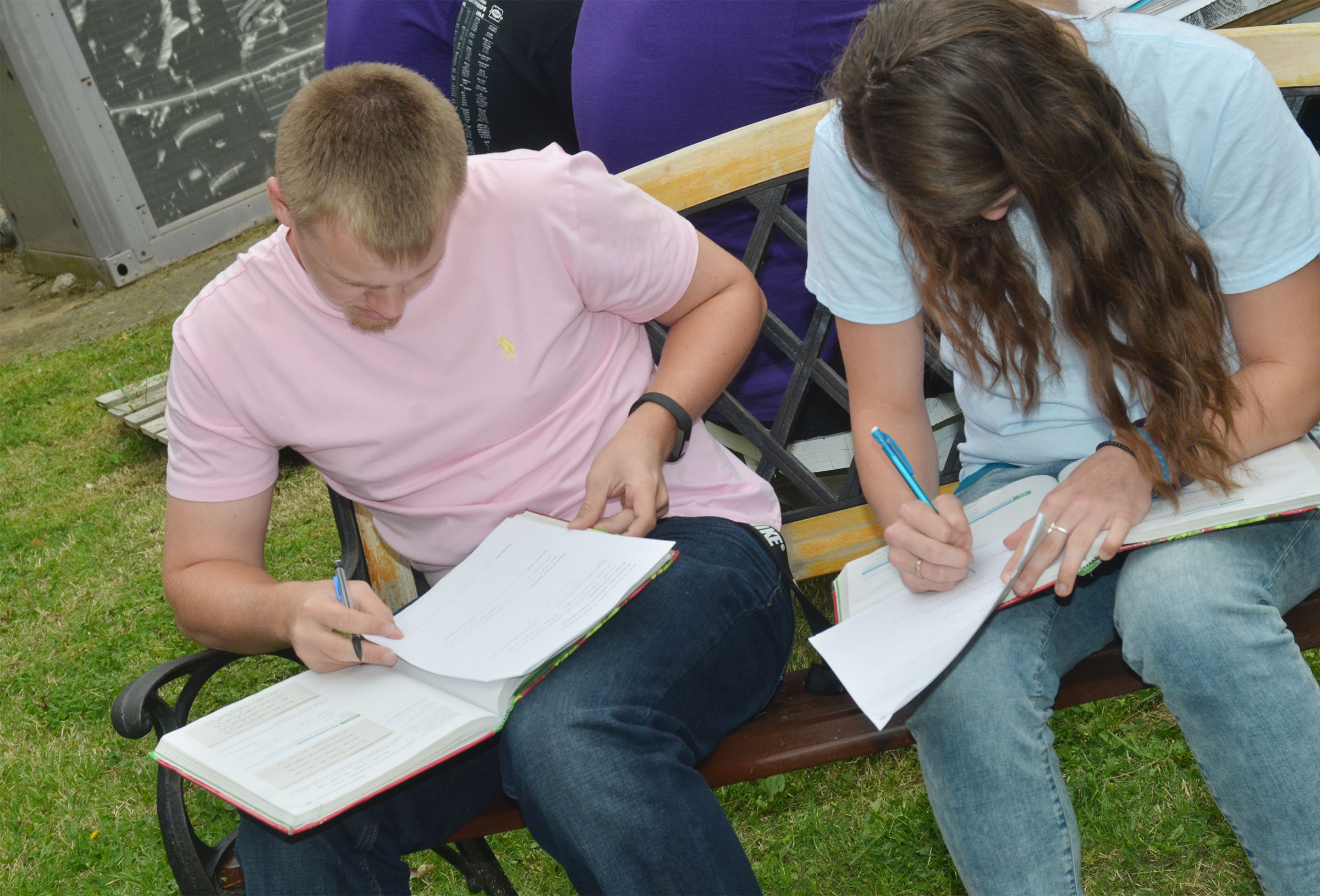 CHS junior Wyatt Houk, at left, and senior Caylie Blair work on their homework while having class outside.