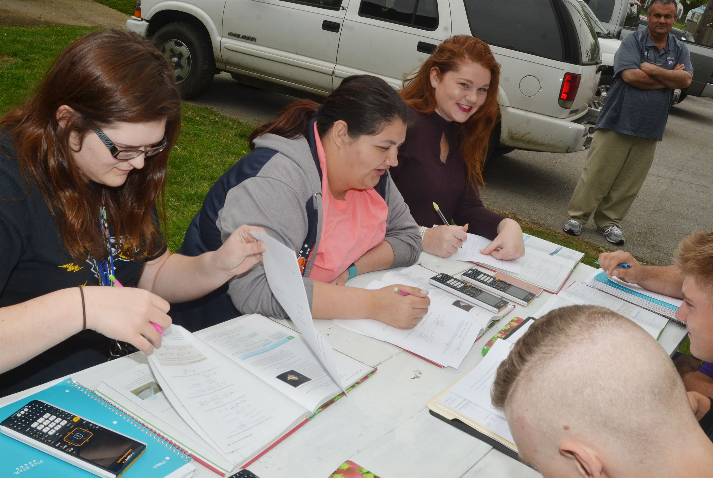 CHS seniors, from left, Vera Brown, Laura May Gutierrez and Mallory Haley work on their homework while having class outside, as math teacher Kevin Rafferty observes.