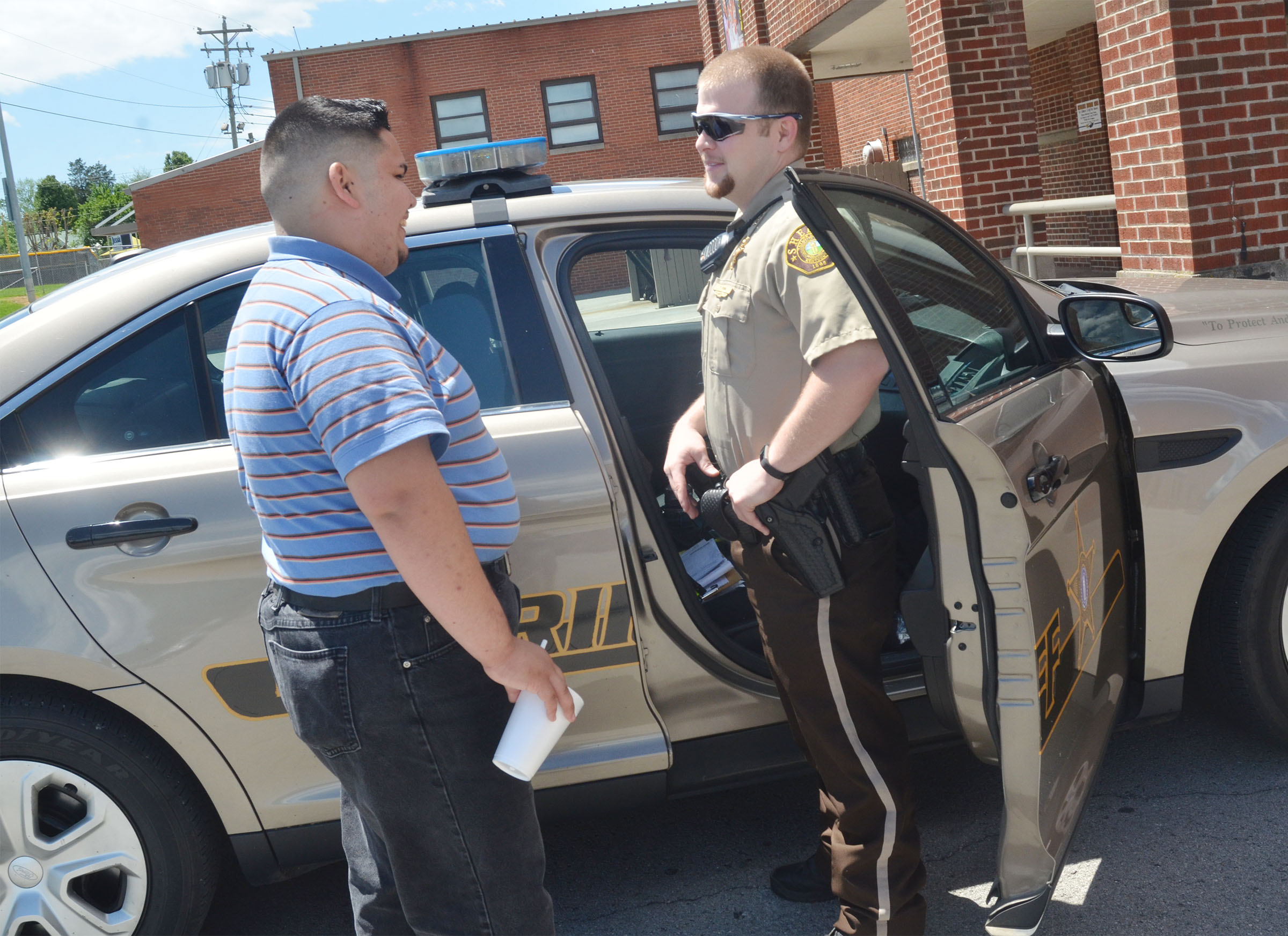 Taylor County Sheriff's Deputy Tyler Finn shows CHS senior Robert Tungate his sheriff's vehicle.