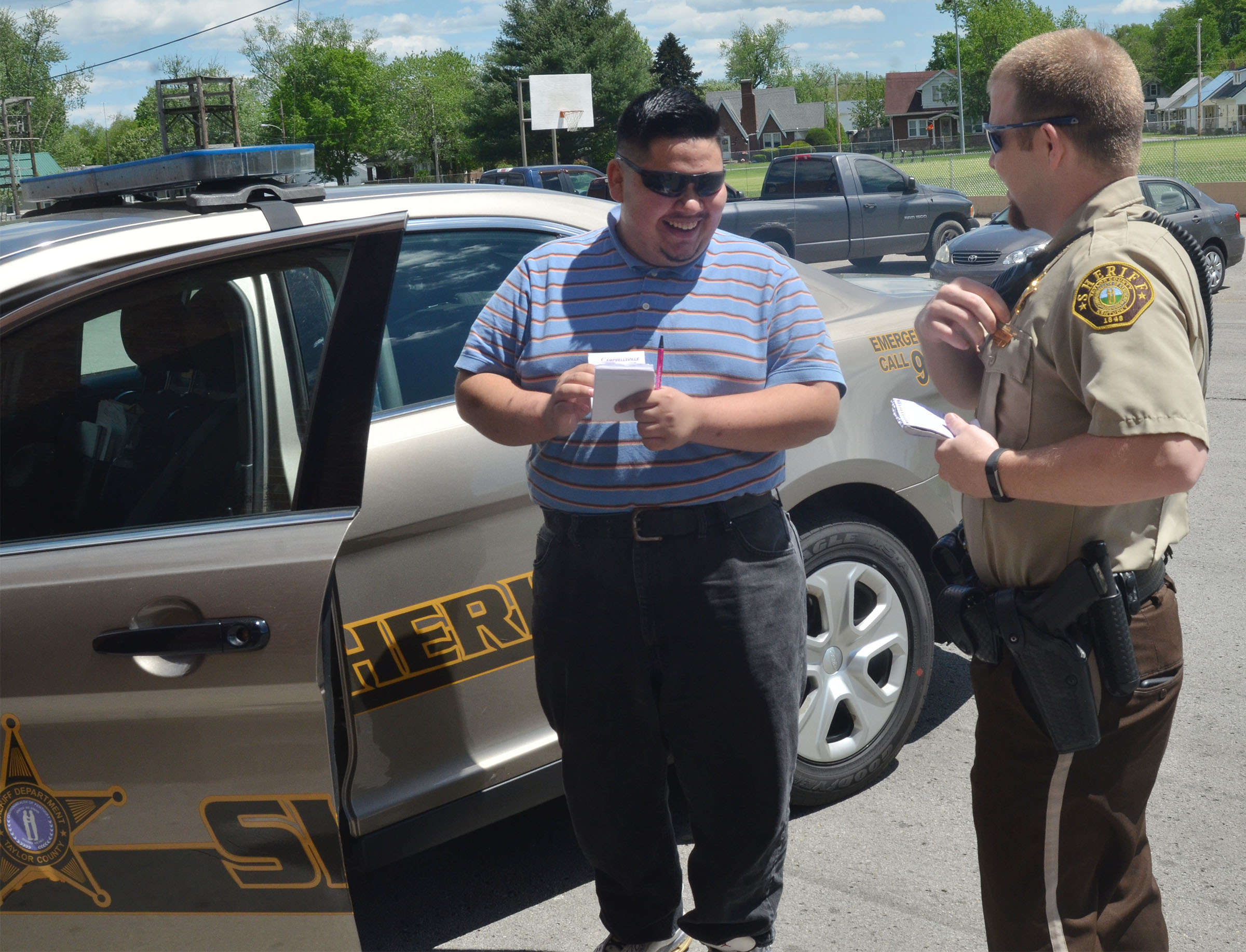 CHS senior Robert Tungate and Taylor County Sheriff's Deputy Tyler Finn compare notebooks that they keep in their pockets.