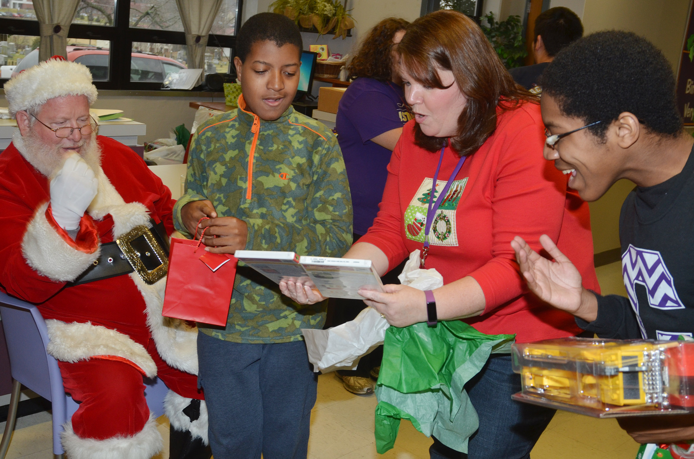 Campbellsville Middle School Guidance Counselor Beth Wiedewitsch helps CHS sophomore Chris Moran, at left, open his gift from Santa. At right is CHS sophomore Travis Nash.