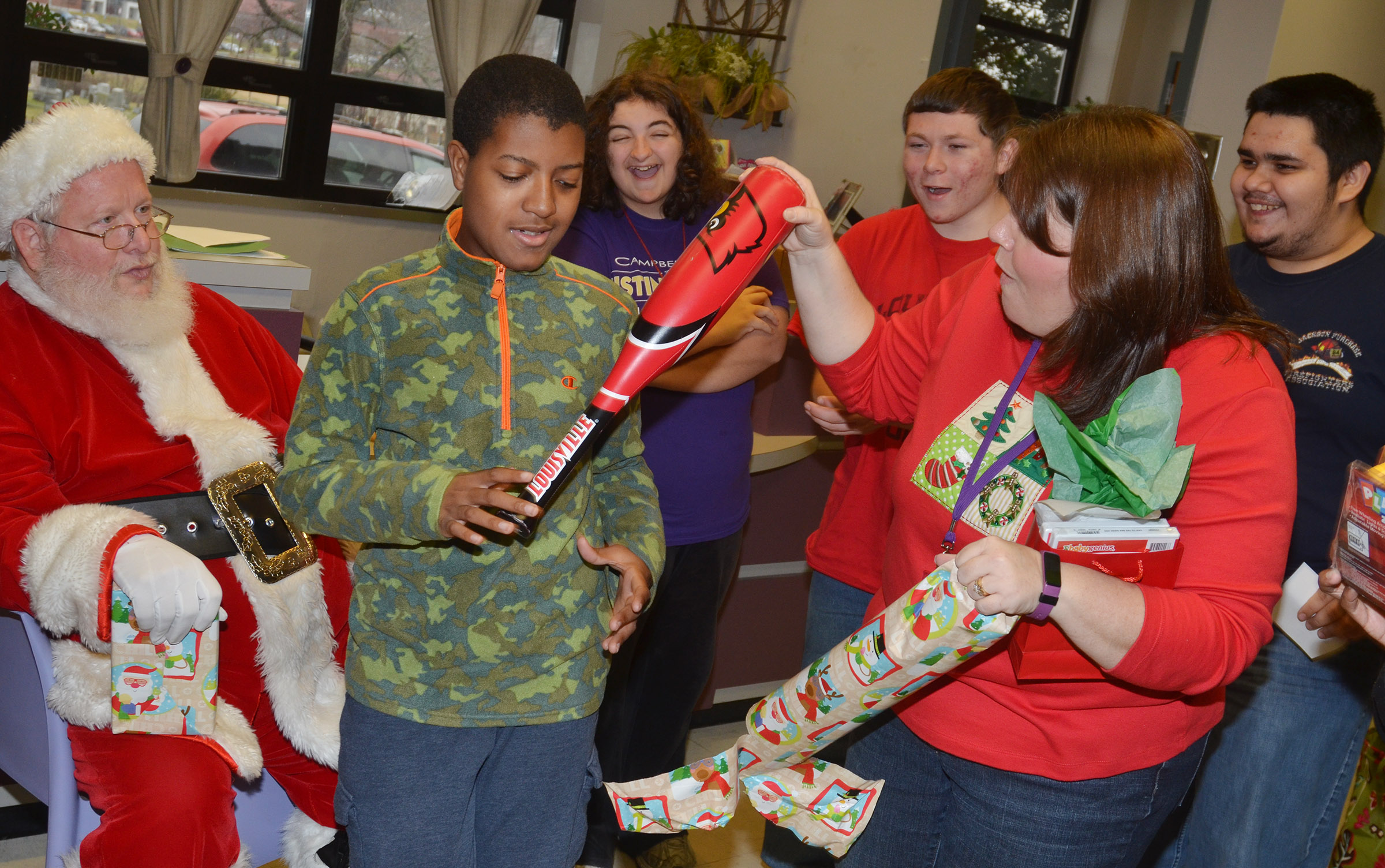 Campbellsville Middle School Guidance Counselor Beth Wiedewitsch helps CHS sophomore Chris Moran, at left, open a baseball bat he received from Santa.