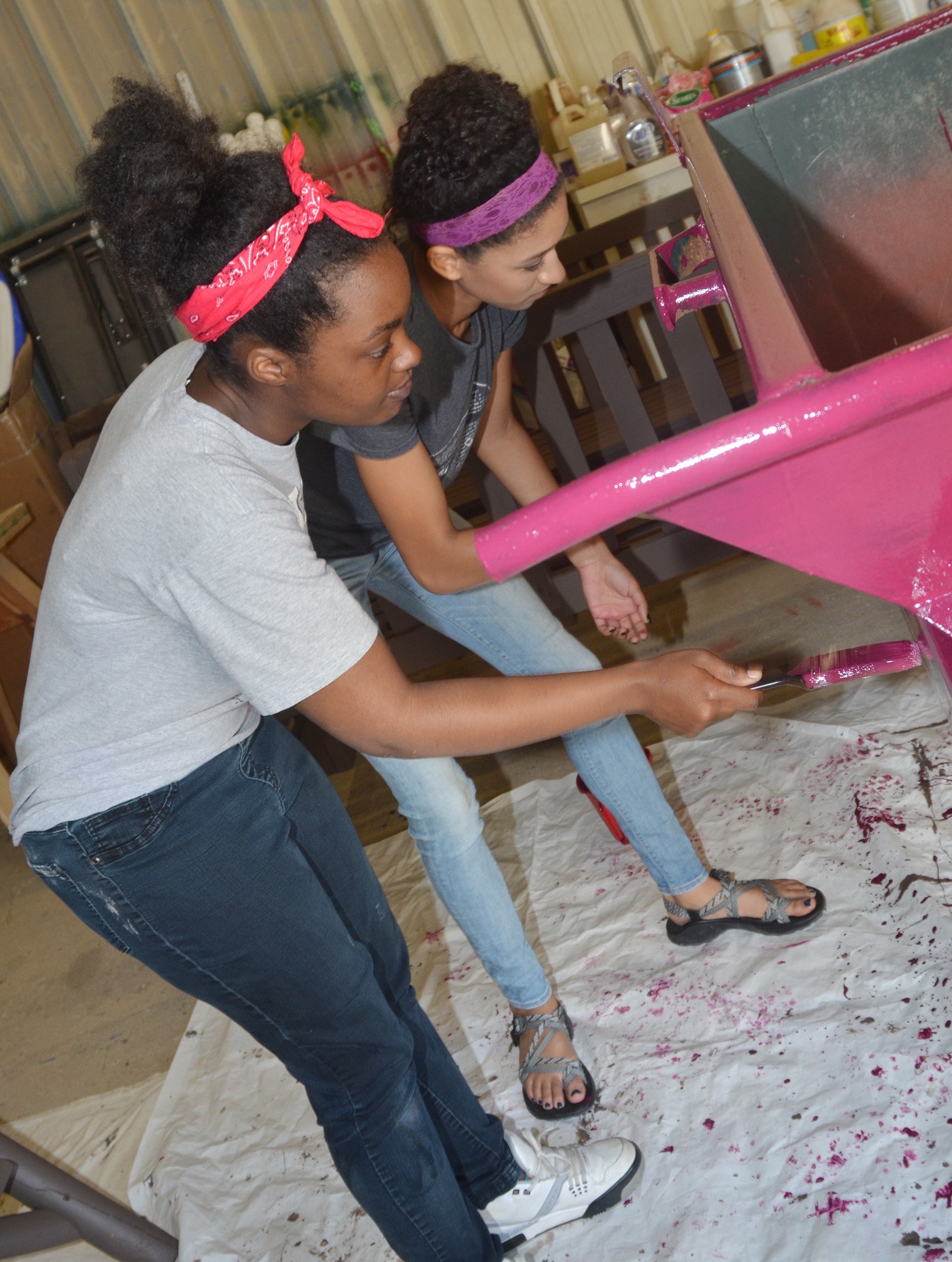 CHS seniors Tonika Spaulding, at left, and Lexi Shears paint a dumpster at Campbellsville University.