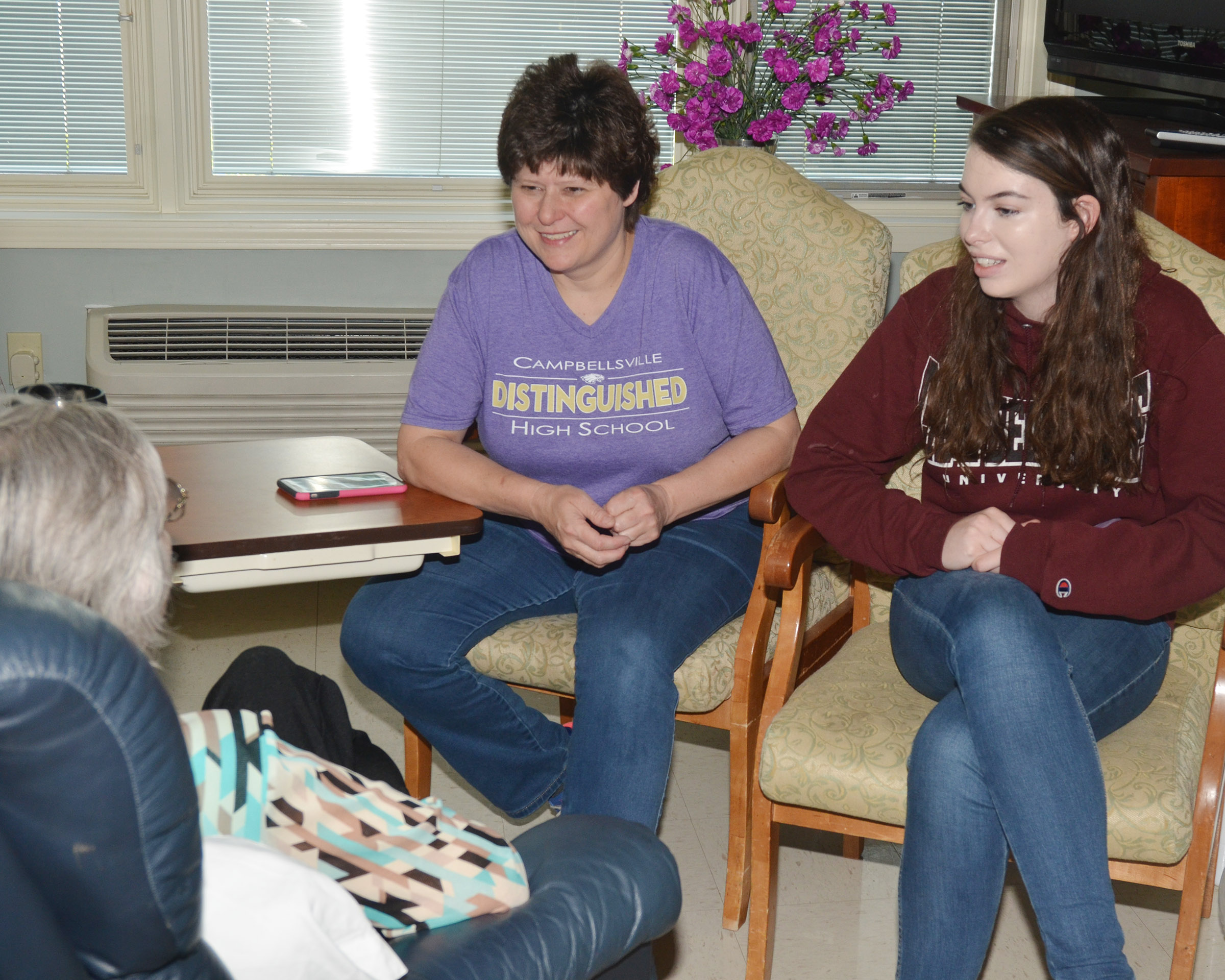 CHS Media Specialist Valerie Davis, at left, and senior Laura Lamb visit with Grandview residents.