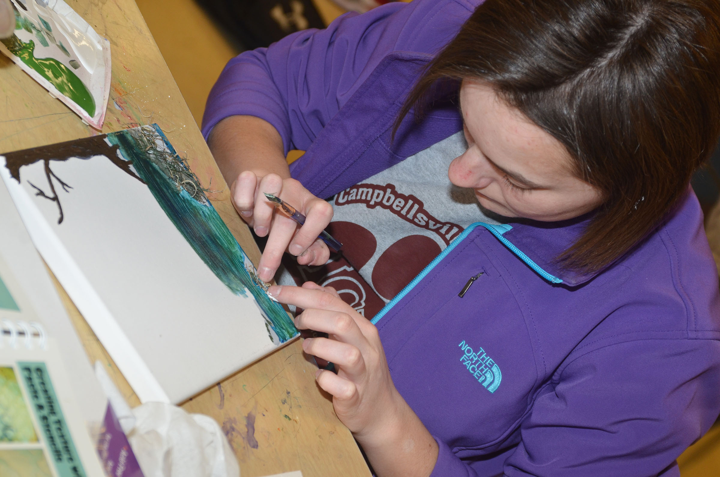 CHS specialized art student Kyrsten Hill, a senior, adds texture to her painting.