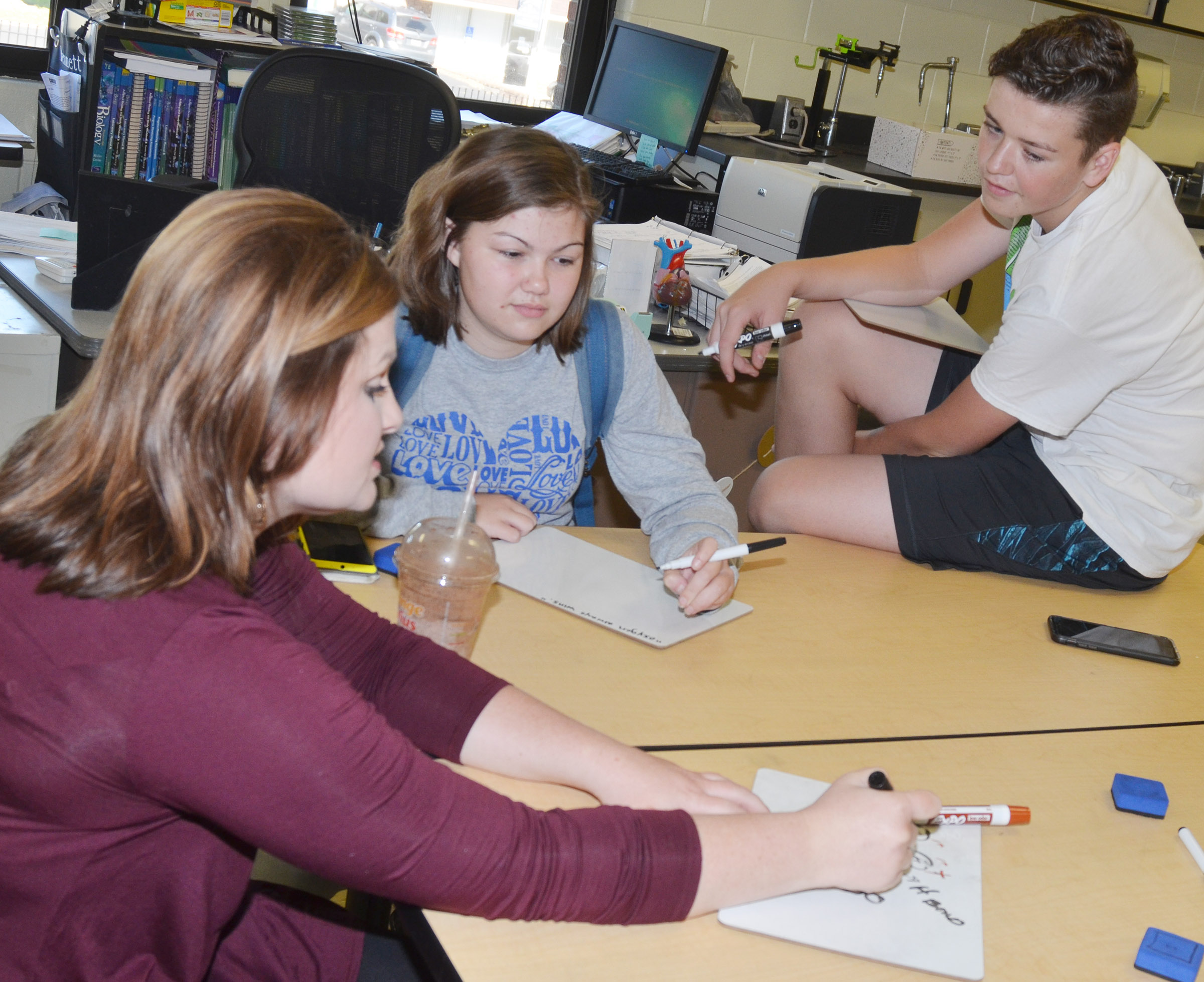 CHS teacher Lauren Bennett helps sophomores Shelby Smith, at left, and Gavin Johnson understand a science concept.