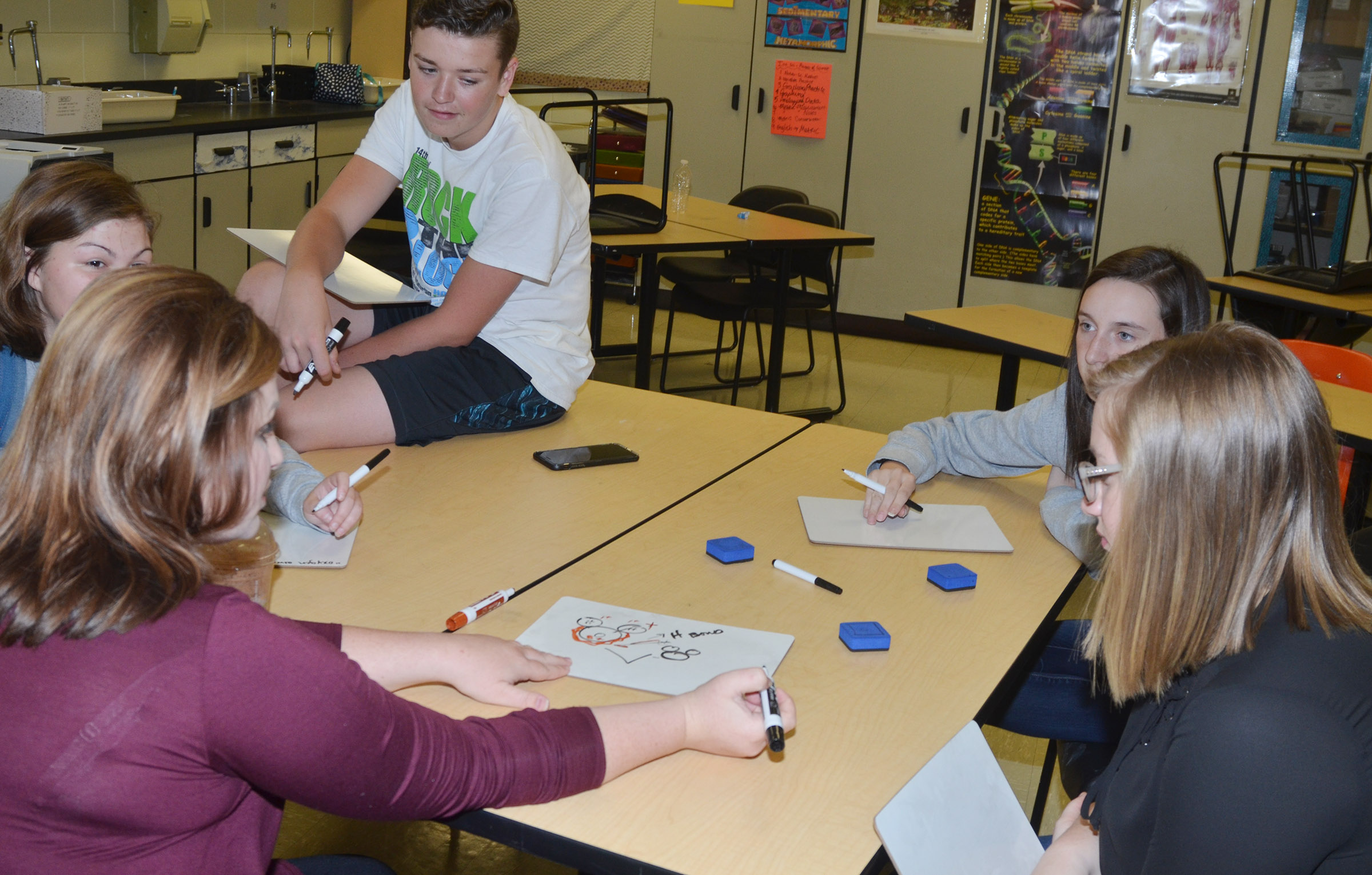CHS teacher Lauren Bennett helps sophomores, from left, Shelby Smith, Gavin Johnson, Zoe McAninch and Samantha Jackson understand a science concept.