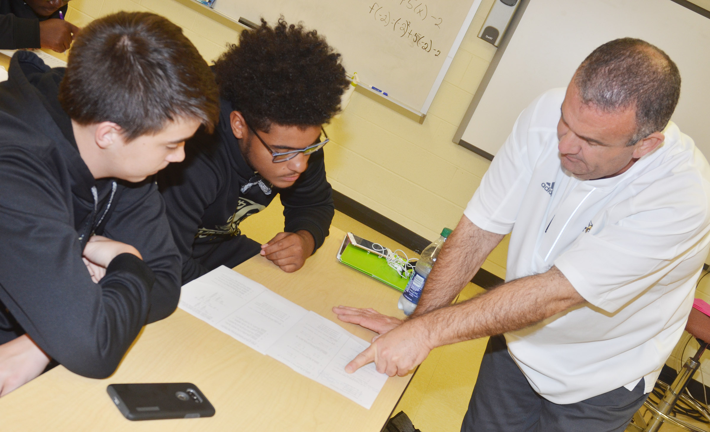 CHS teacher Kevin Rafferty helps sophomores Cole Kidwell, at left, and Braden Paige with a math problem.