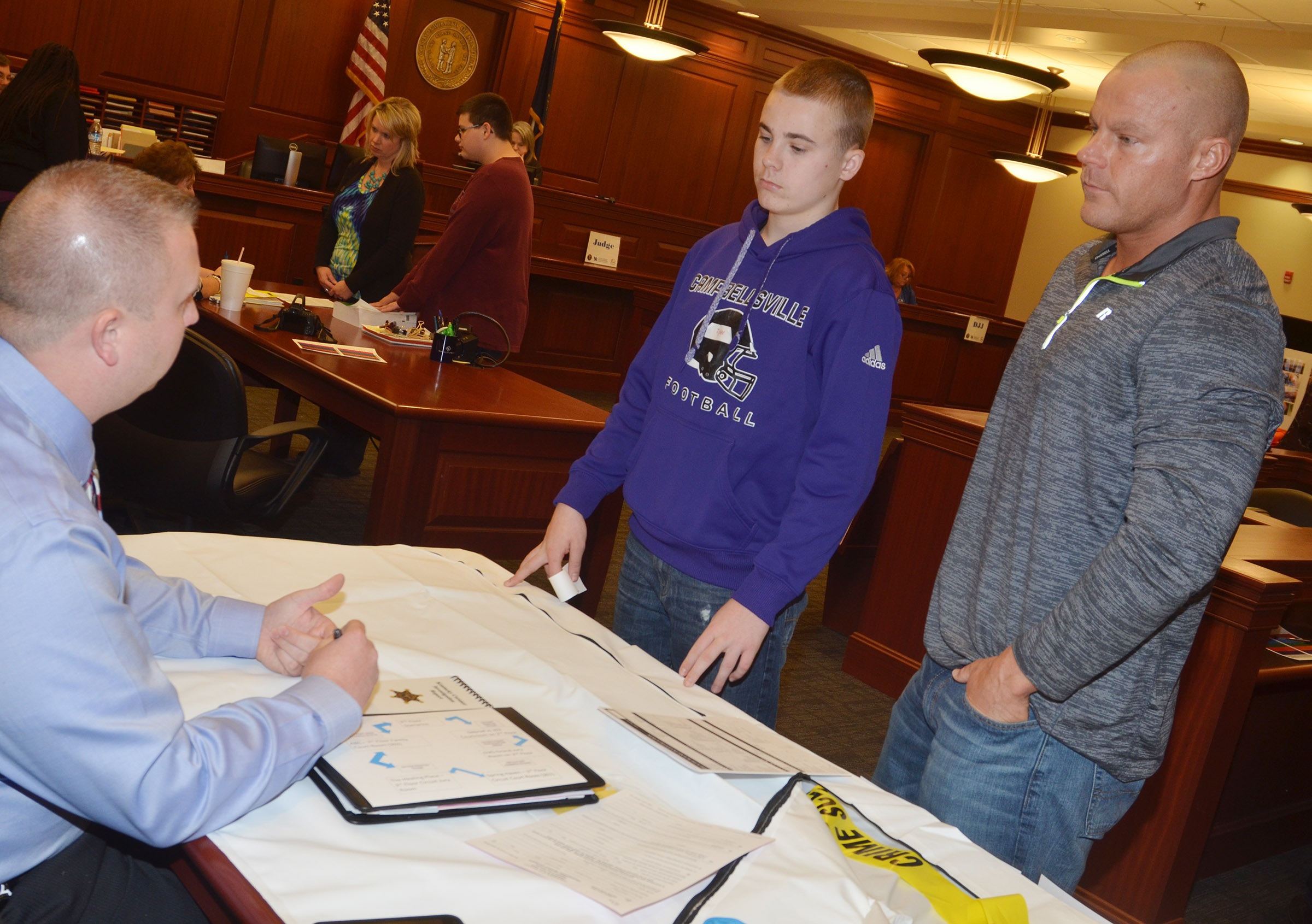 "CHS freshman Tyler Gribbins and his father, Robbie, meet with Taylor County Coroner Daniel Cook as part of the ""Truth or Consequences"" scenario."