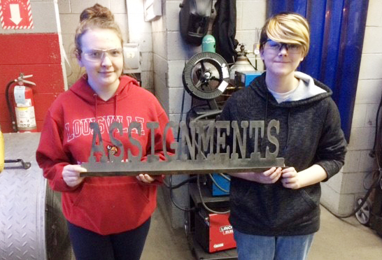 CHS juniors Katelyn Walker, at left, and Chloe Decker made this metal sign with a CNC plasma cutter.