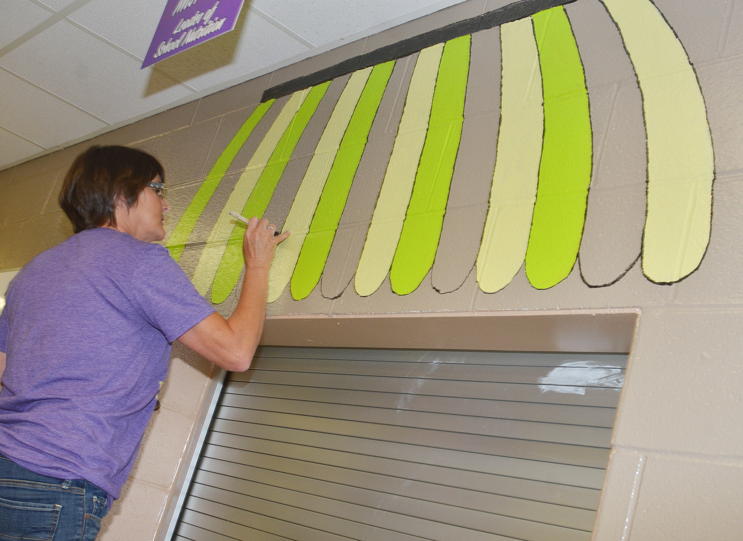 Bobbi Faulkner, a cafeteria worker, paints the CMS/CHS cafeteria.