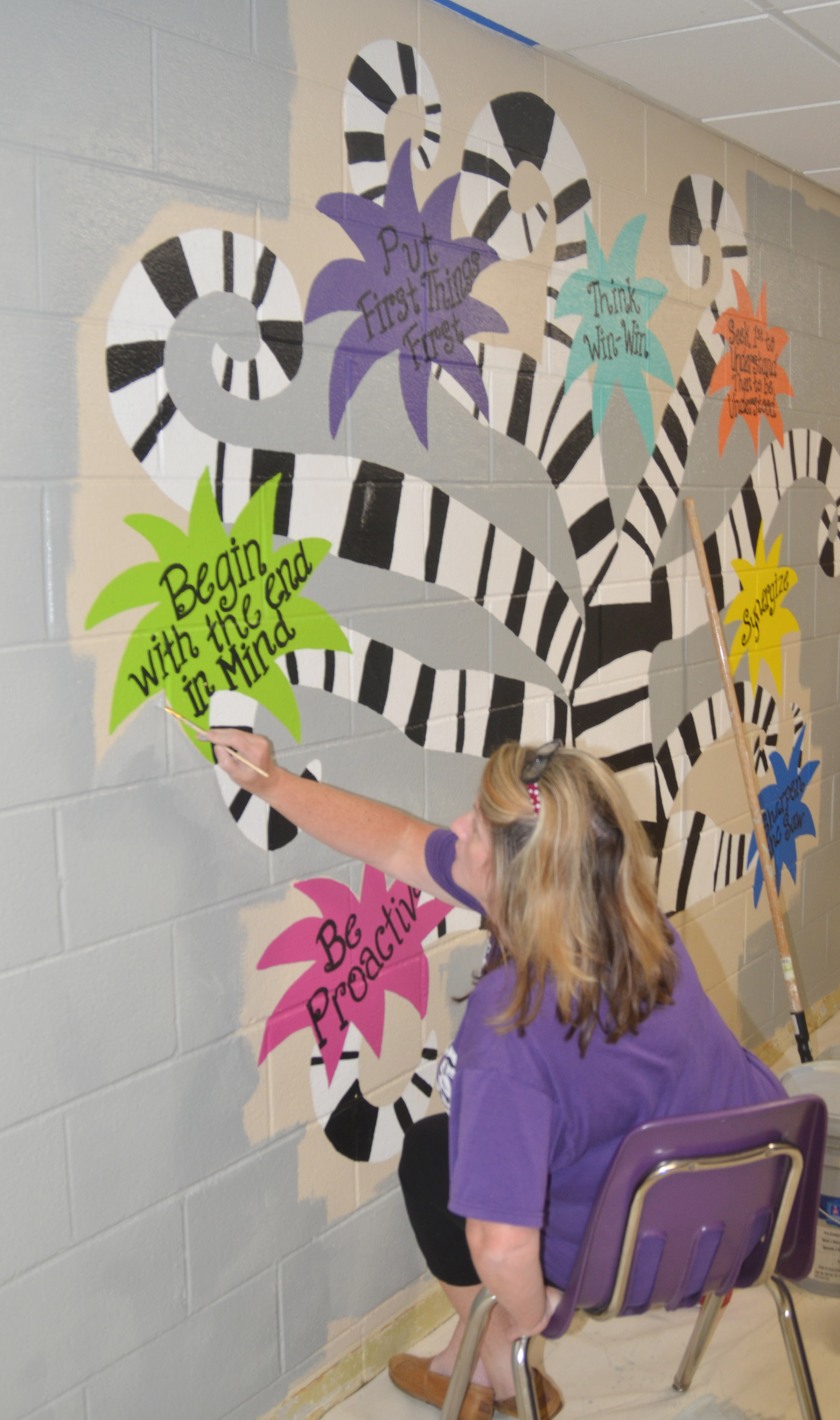 CES teacher Donna White paints the wall in her hallway.