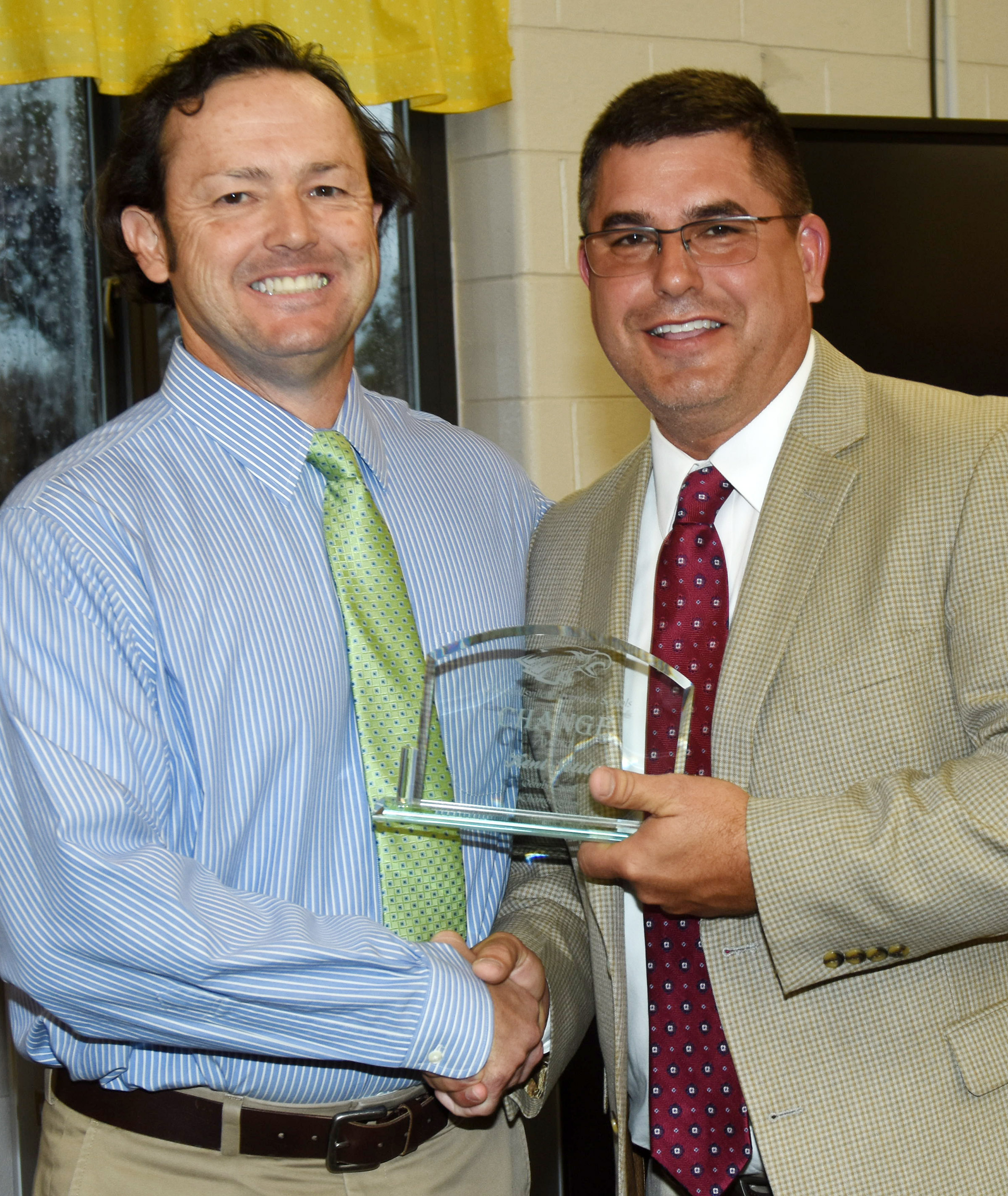 Campbellsville Independent Schools Superintendent Kirby Smith, at right, honors CIS Chief Academic Officer Kent Settle with the certified Change Award.