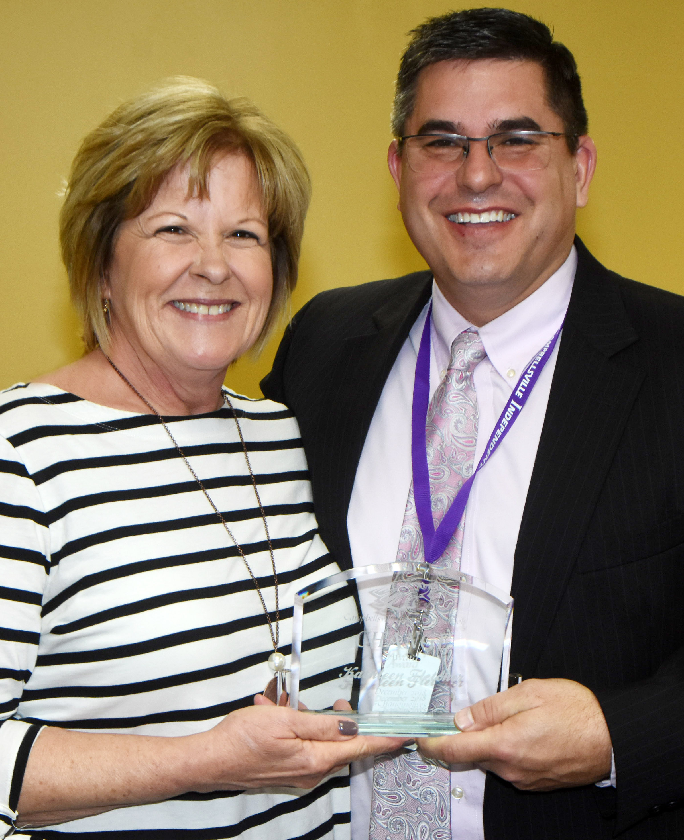 Campbellsville Independent Schools Superintendent Kirby Smith honors Campbellsville FRYSC Advisory Council member Kathleen Fletcher with the community Change Award.