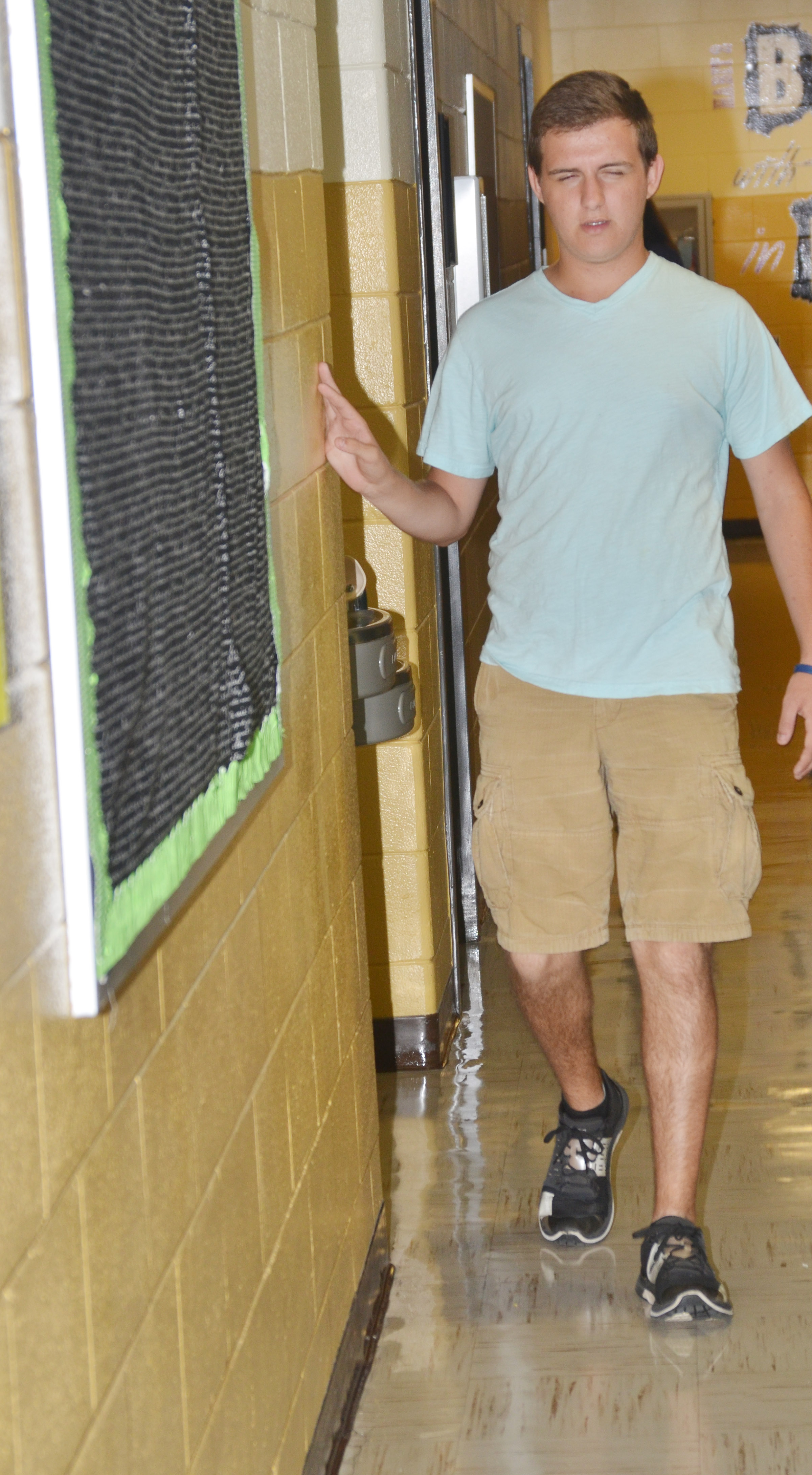 CHS senior Austin Fitzgerald prays as he walks down the hallway at his school.