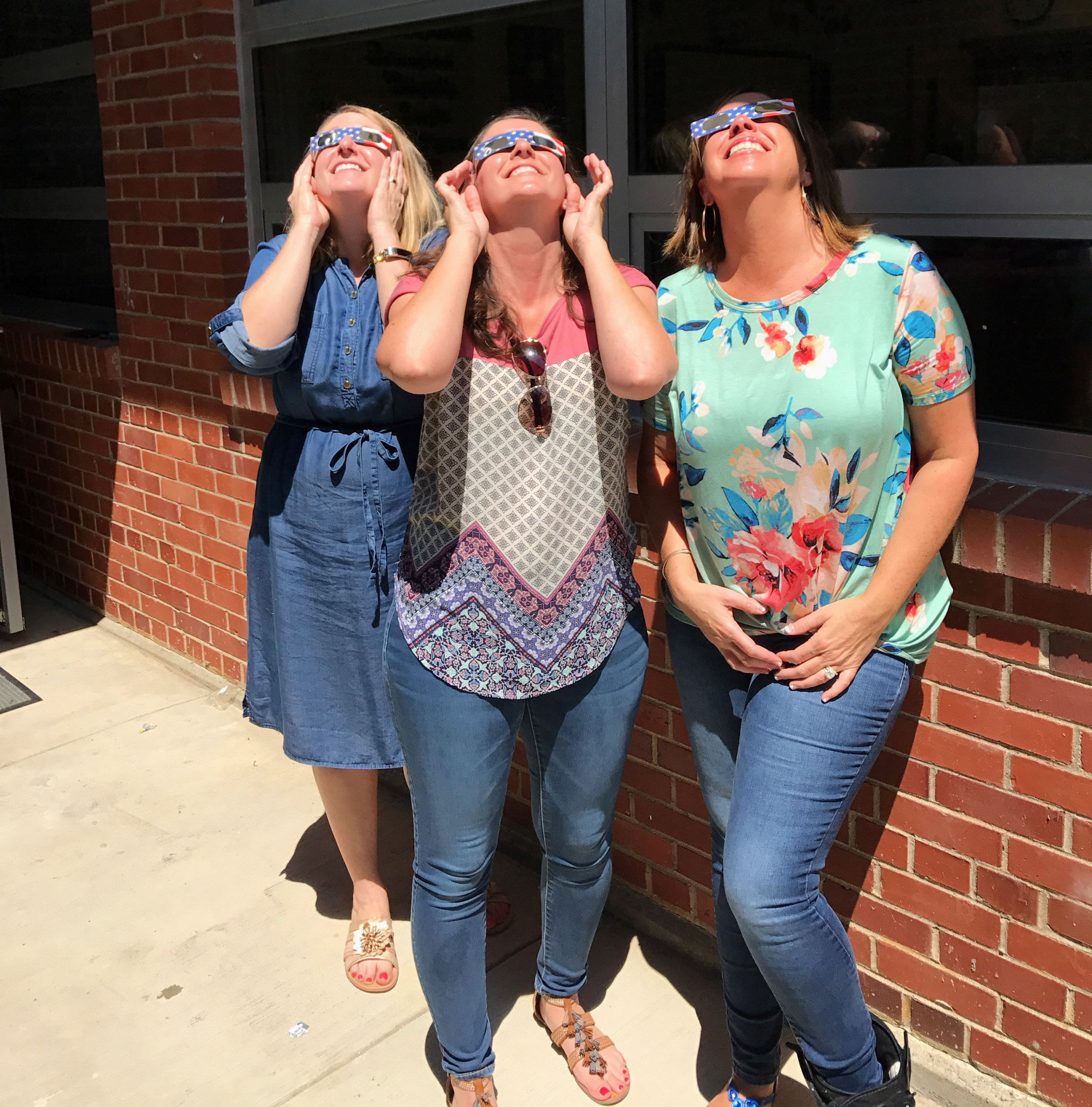 CES teachers, from left, Laura Dicken, Adrienne Hash and Farrah Hord view the eclipse.