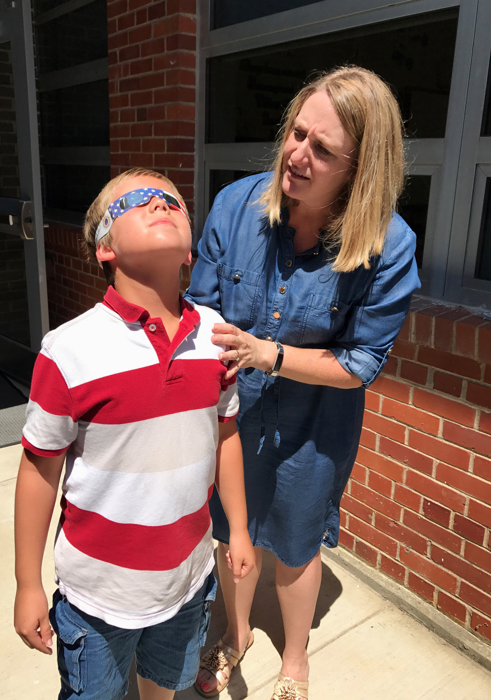 CES teacher Laura Dicken makes sure third-grader Evan Cundiff is wearing his solar glasses.