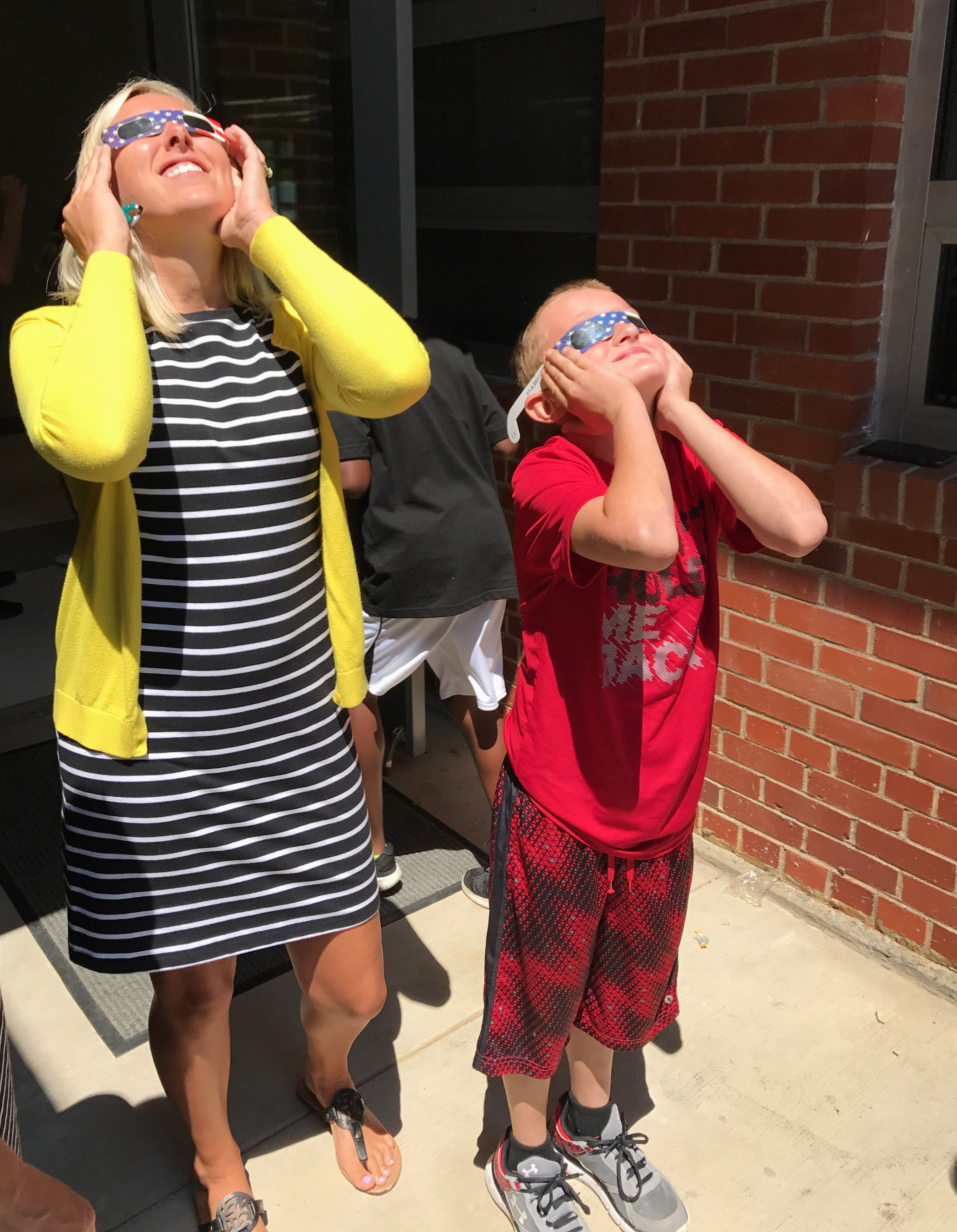 CES teacher Hannah Jones watches the eclipse with fourth-grader Ryder Murphy.