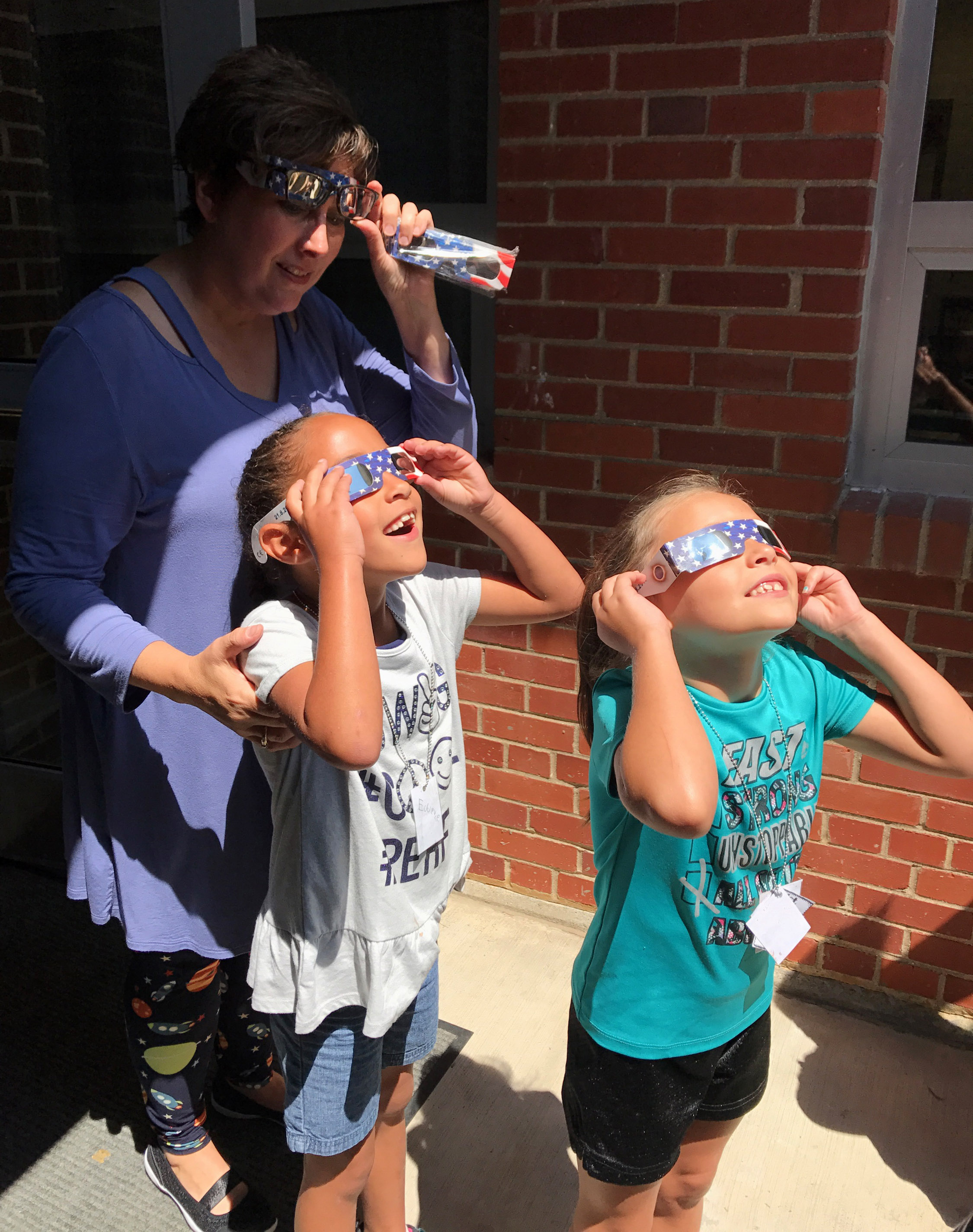 CES second-grade teacher Lynne Horn views the eclipse with her students.