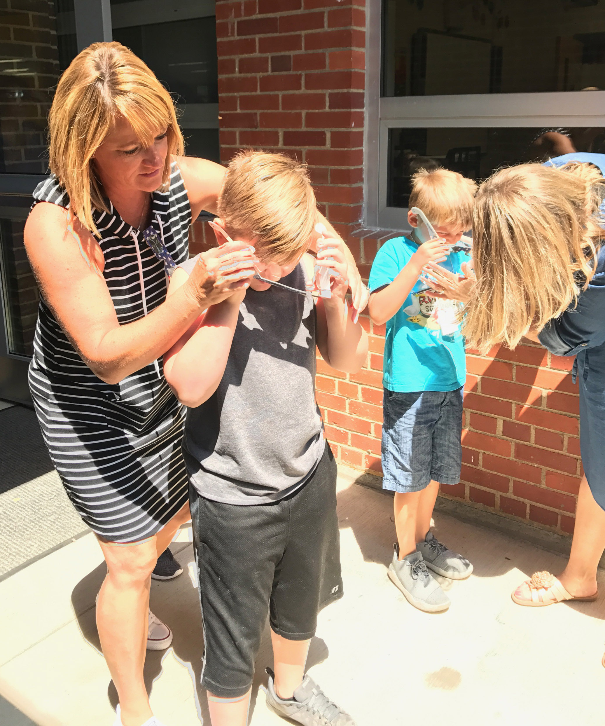 CES teacher Vanessa Adkins helps second-grader Tommy Caswell put on his solar glasses.