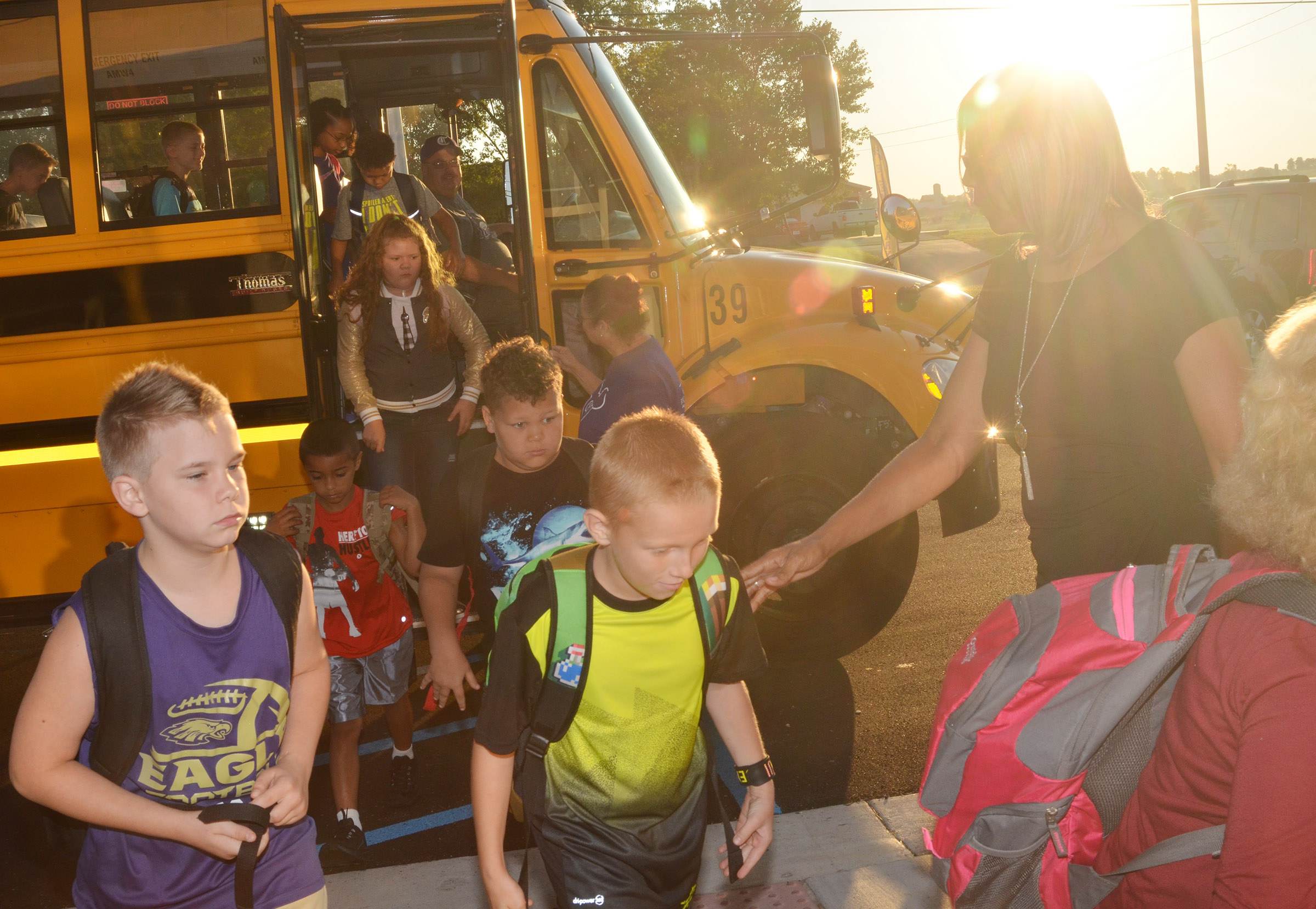 CES Assistant Principal Doretha Sanders helps students off the school bus.